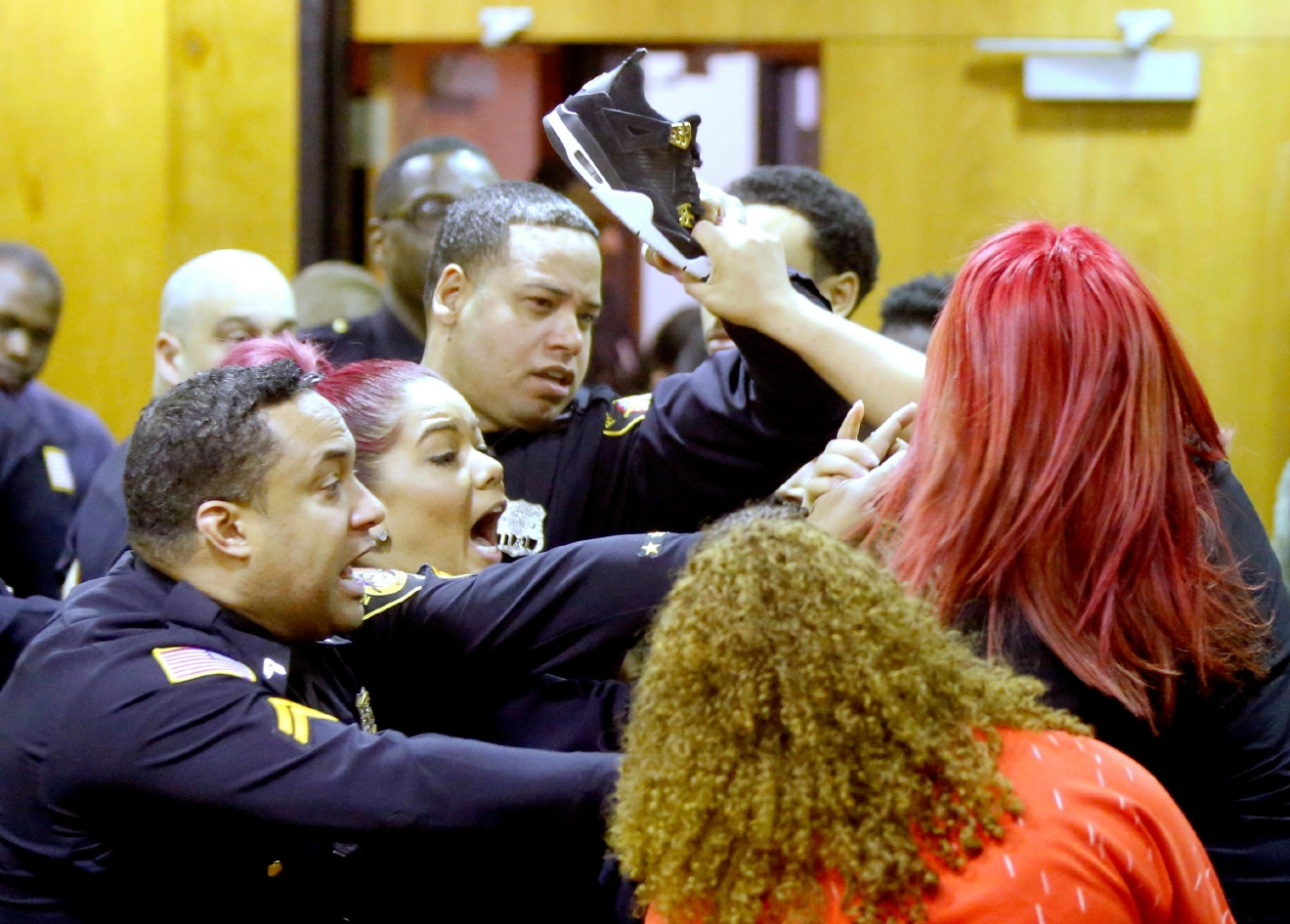 Sheriff's Deputies keep Debora Hernandez, right, the mother of Antonio Vega's daughter, from hitting a defendant's family member with her shoe after an altercation between the two groups broke out at the end of a hearing where Clarence Williams and Gerry Thomas made their appearances for murder, Friday, March 24, 2017, in Paterson, N.J.   (Aristide Economopoulos /NJ Advance Media via AP, Pool)