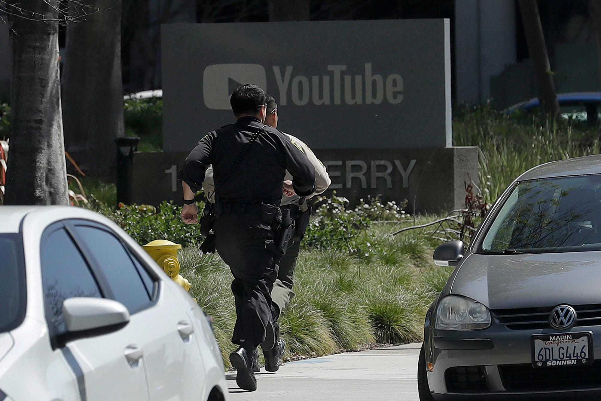Officers run toward a YouTube office in San Bruno, Calif., Tuesday, April 3, 2018. Police and federal officials responded a shooting Tuesday at YouTube headquarters in Northern California. (AP Photo/Jeff Chiu)