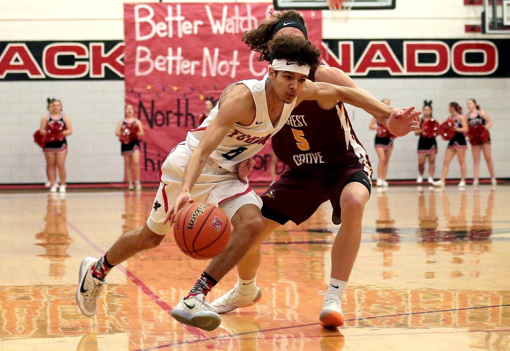 North Medford senior Darrius Wells races past Forest Grove defender Eli Leto on the Opening night of the 2018 Abby's Holiday Classic at North Medford High on Thursday.(PHOTO BY:  LARRY STAUTH JR)