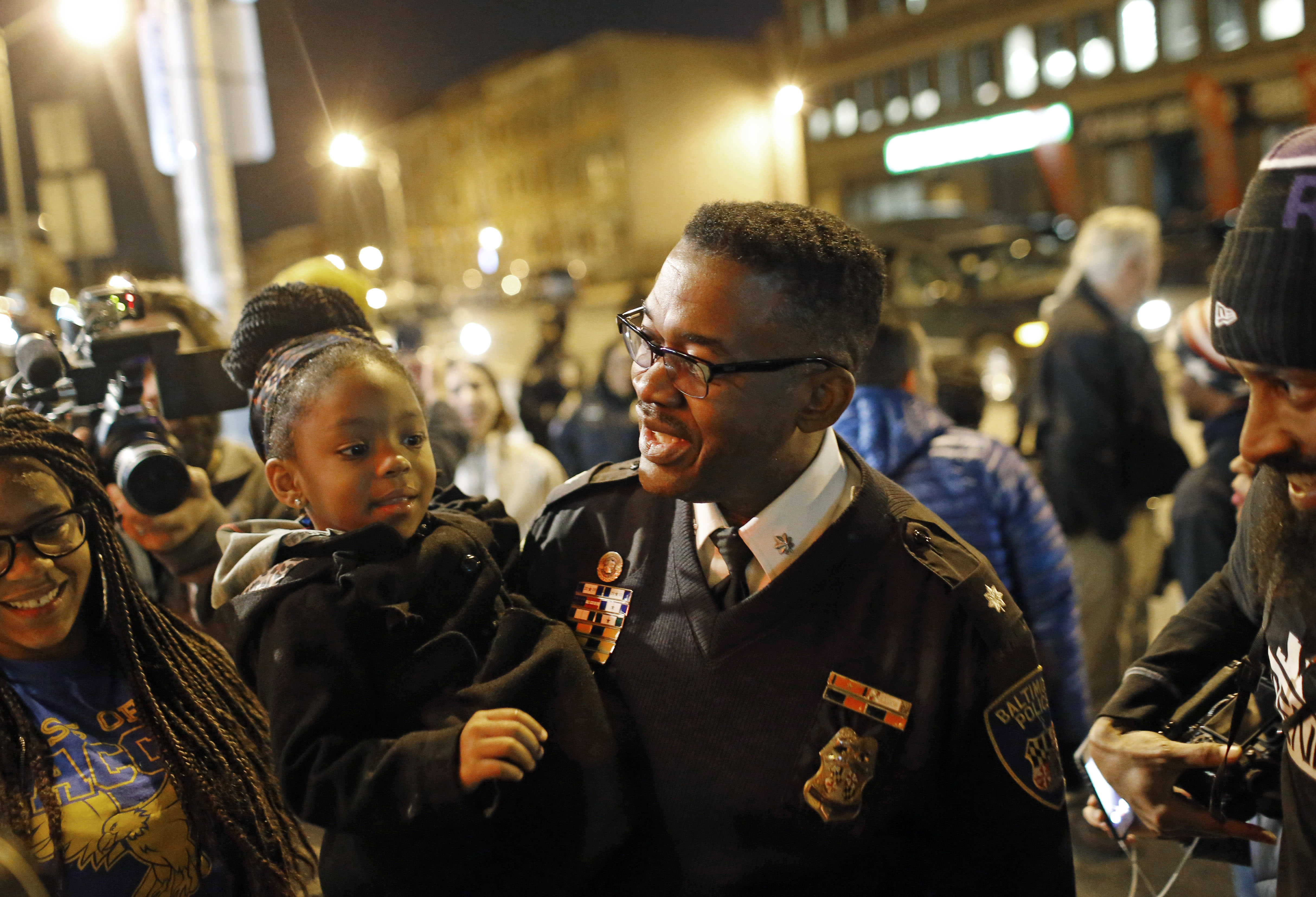 Baltimore Police Department Lt. Col. Melvin Russell, right, holds Paris Brown, 3, as he visits with residents near the intersection of North and Pennsylvania Avenues, the site of unrest following the funeral of Freddie Gray, Wednesday, Dec. 16, 2015, in Baltimore. Peaceful protests took place in response to a hung jury and mistrial for Officer William Porter, one of six Baltimore city police officers charged in connection to Gray's death. (AP Photo/Patrick Semansky)