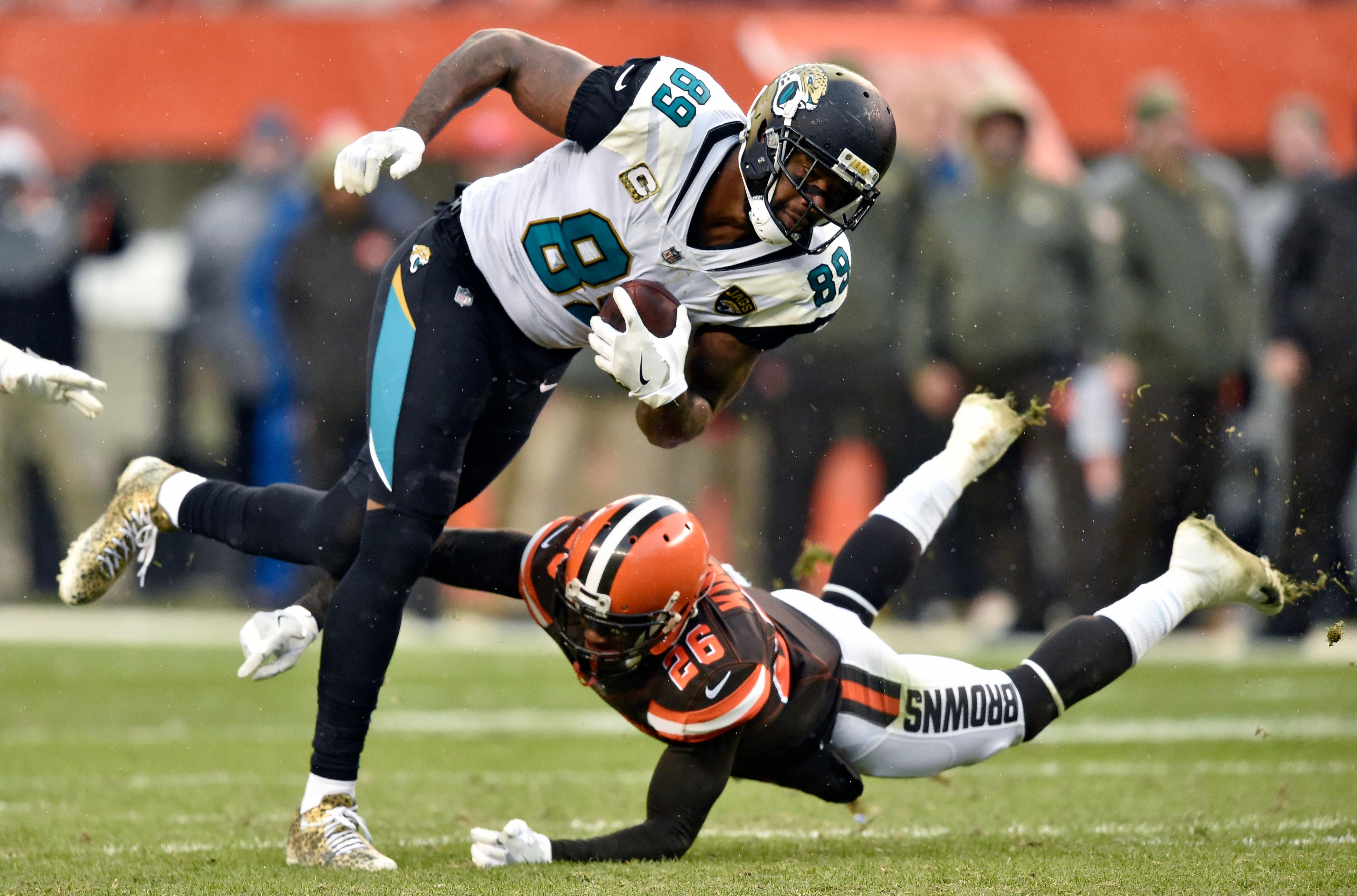 Jacksonville Jaguars tight end Marcedes Lewis (89) is tackled by Cleveland Browns strong safety Derrick Kindred (26) in the first half of an NFL football game, Sunday, Nov. 19, 2017, in Cleveland. (AP Photo/David Richard)