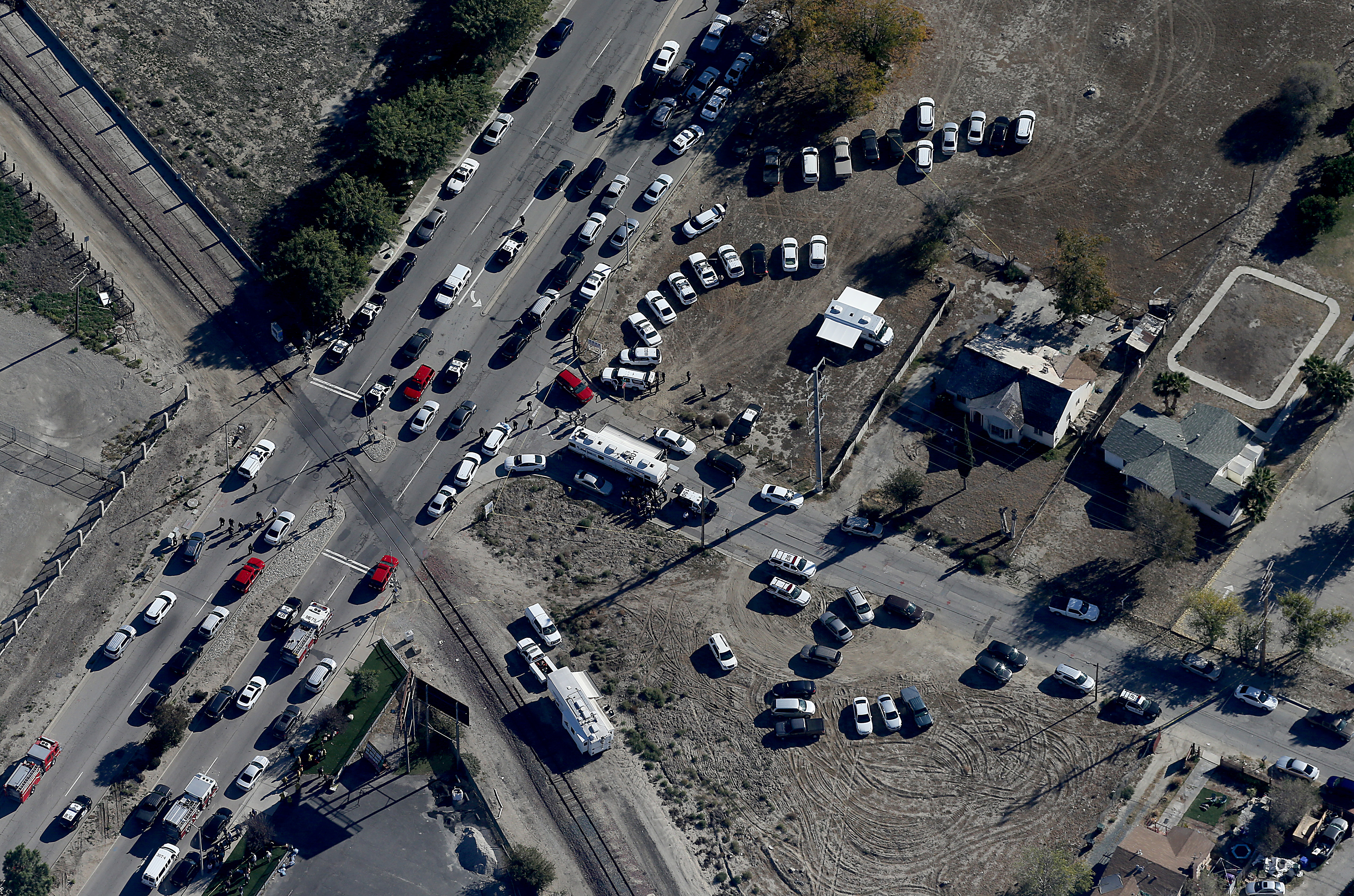 Police and emergency vehicles line Waterman Avenue in front of the Inland Regional Center in San Bernardino, Calif., scene of a mass shooting on Wednesday, Dec. 2, 2015.  As many as three gunmen believed to be wearing military-style gear opened fire Wednesday at the Southern California social services center. Authorities said the shooting rampage killed multiple people and wounded others.  (Luis Sinco/Los Angeles Times via AP)