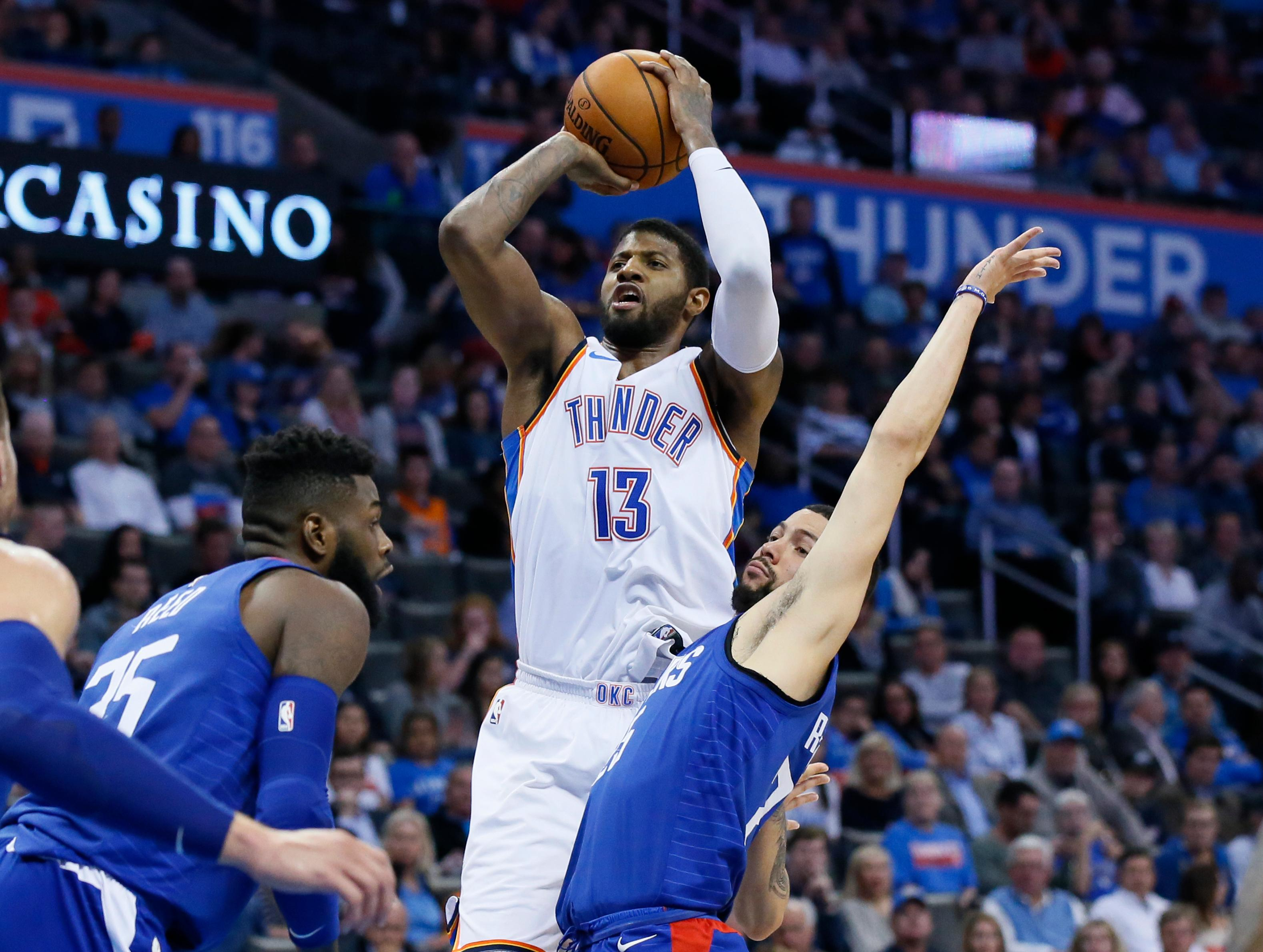 Oklahoma City Thunder forward Paul George (13) shoots between Los Angeles Clippers center Willie Reed, left, and guard Austin Rivers, right, in the third quarter of an NBA basketball game in Oklahoma City, Friday, Nov. 10, 2017. Oklahoma City won 120-111. (AP Photo/Sue Ogrocki)
