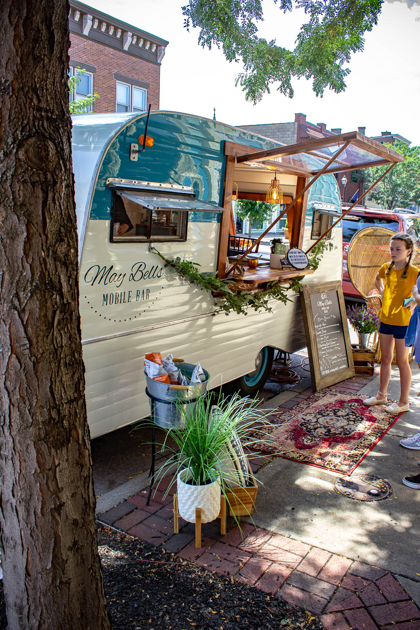 May Bells Mobile Bar is a light blue, '68 Scotty Serro camper that's all dolled up in a rustic, charming style to provide farm-fresh beverages everywhere it goes. Meggie Wainscott Martin is the director of operations who got into the business after growing up in the restaurant industry. May Bells is an extension of the Marian Historic Venue, which is a southern home-turned-event space that dates back to 1886. / Image: Katie Robinson, Cincinnati Refined // Published: 8.9.19<br>