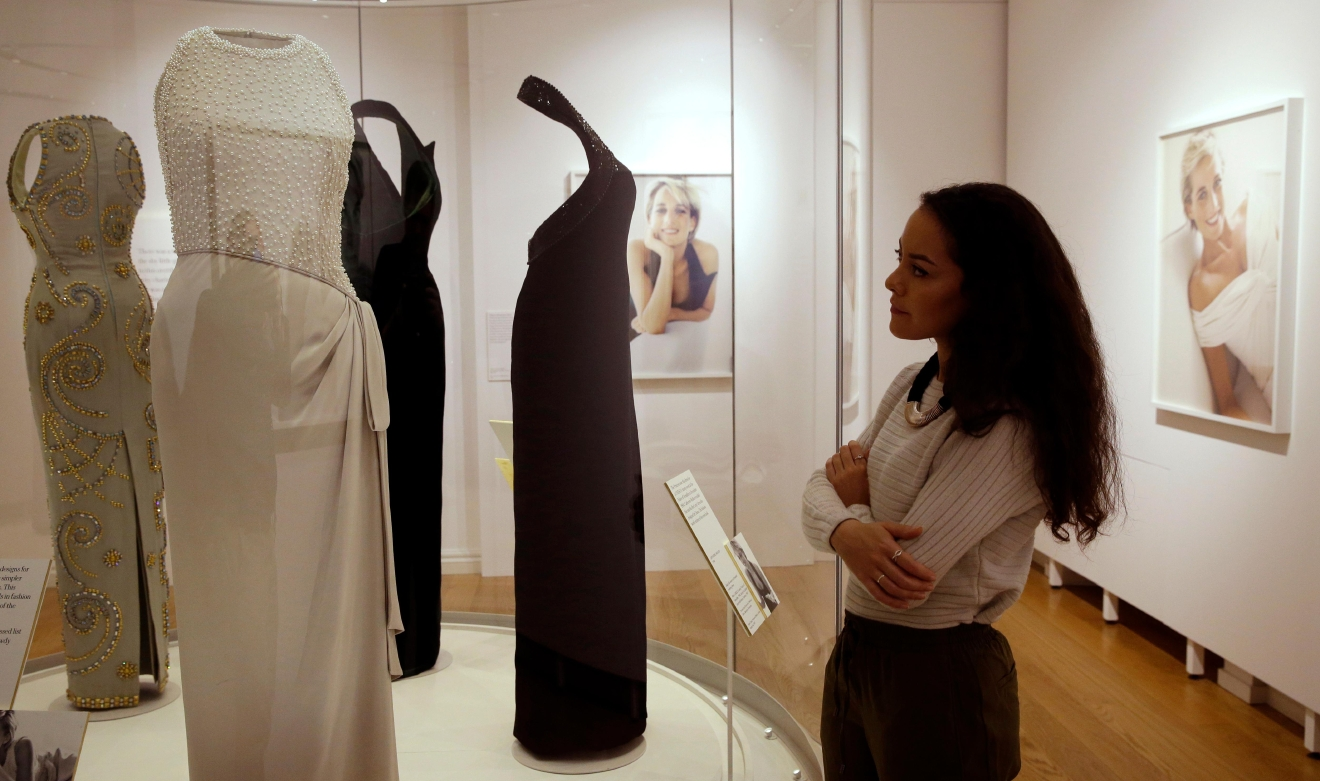 "A member of staff at Kensington Palace looks at a Catherine Walker grey silk satin dress worn by Diana, Princess of Wales at a Vanity Fair photo shoot by Mario Testino 1997, and a state banquet with the King of Malaysia in 1992, during a media preview of an exhibition of 25 dresses and outfits worn by Diana, entitled ""Diana: Her Fashion Story"" at Kensington Palace in London, Wednesday, Feb. 22, 2017. (AP Photo/Alastair Grant)"