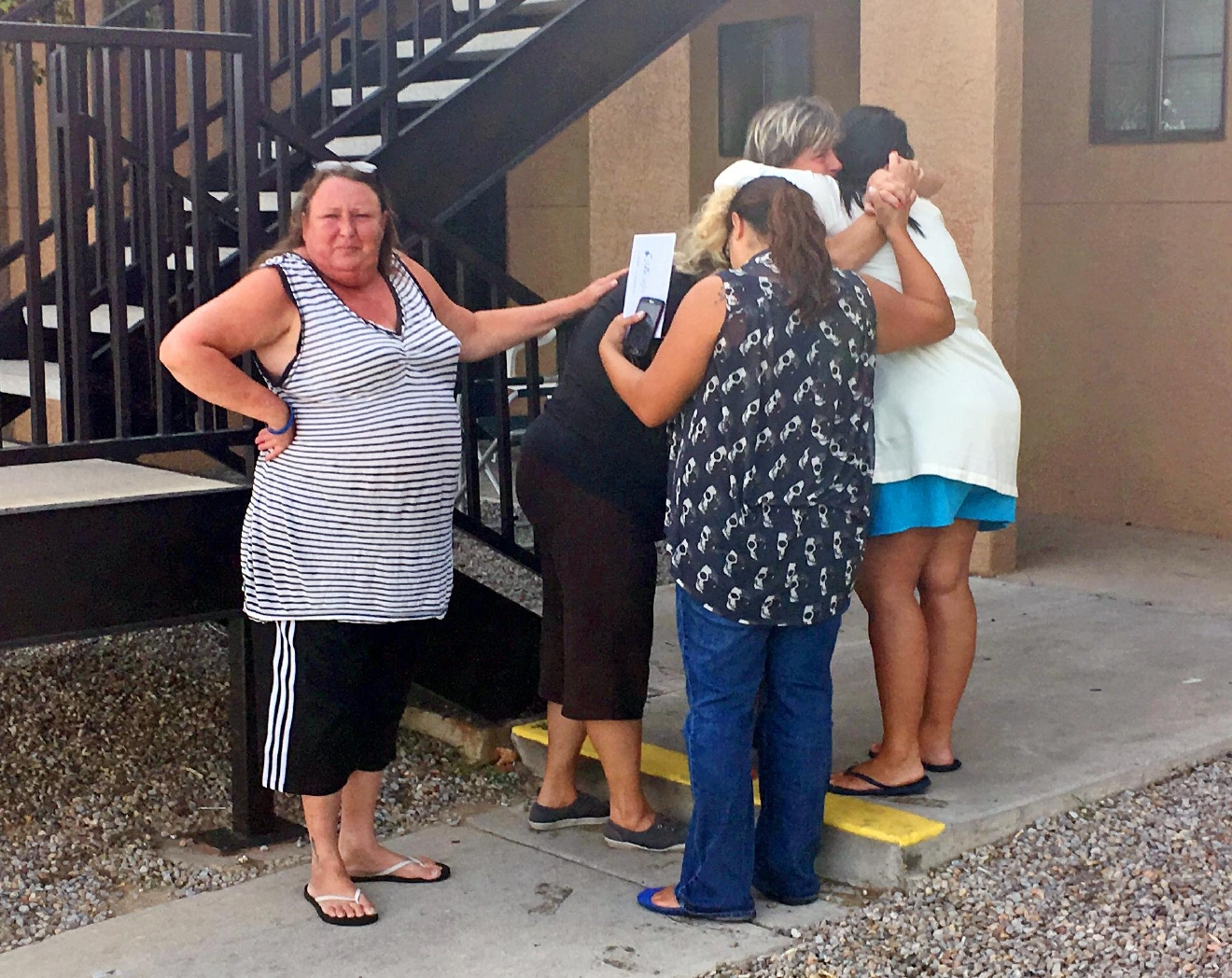 Women mourn near the apartment  in Albuquerque, N.M., Thursday, Aug. 25, 2016, where the body of a 10-year-old girl who police said was sexually assaulted, strangled then dismembered was found. On the day the girl was going to celebrate her 10th birthday, she was found dead Wednesday in her family's apartment by Albuquerque police, her dismembered remains lying under a burning blanket. The girl's mother, 35-year-old Michelle Martens, her 31-year-old boyfriend, Fabian Gonzales, and his 31-year-old cousin, Jessica Kelley, are facing charges. (AP Photo/Russell Contreras)