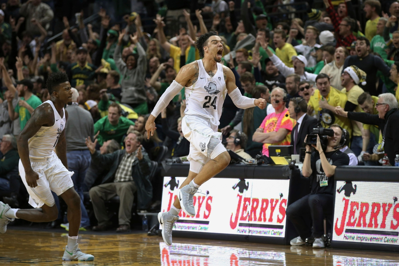 Oregon's Dillon Brooks, center, leaps in the air in celebration after sinking the game winning shot over UCLA in an NCAA college basketball game Wednesday, Dec. 28, 2016, in Eugene, Ore. (AP Photo/Chris Pietsch)