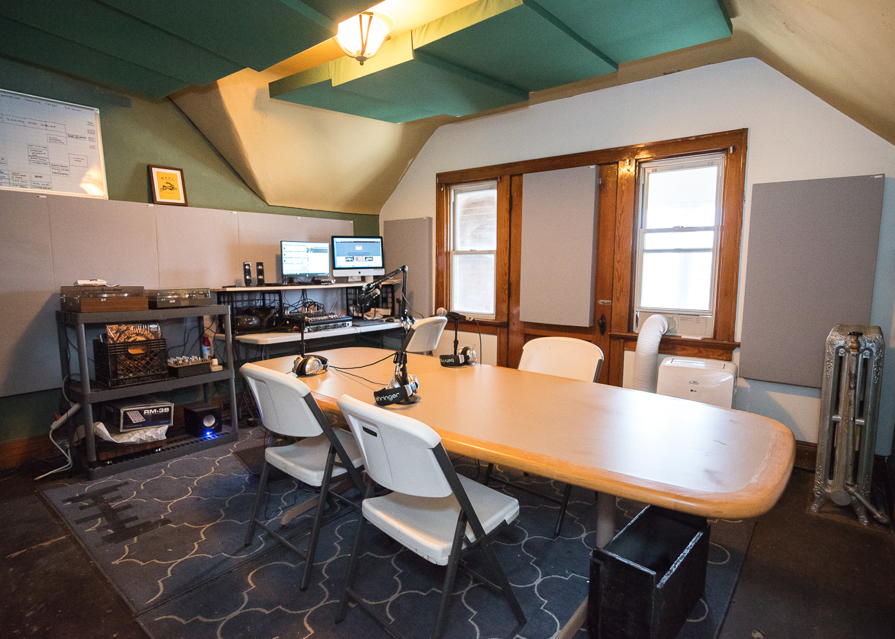 The Main Studio is within a modestly-sized space on the third floor of the building. Microphones rest on a table in the middle of the room for use in podcasting and other recording purposes. Turntables sit beside the soundboard and the station's antenna is just beyond an exterior door that leads to a covered balcony. / Image: Phil Armstrong, Cincinnati Refined // Published: 1.15.18<p></p>