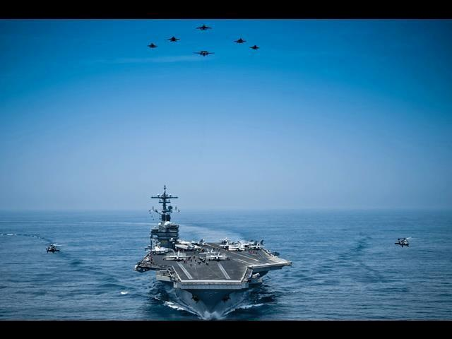 Aircraft from Carrier Air Wing 8 fly in formation over the USS George H.W. Bush in the Arabian Sea, April 29, 2014.