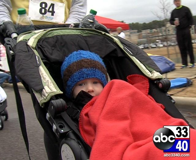 A young boy rides along in a stroller during the 10th Annual Brenda Ladun Conquer Cancer Run, Saturday, March 1, 2014.