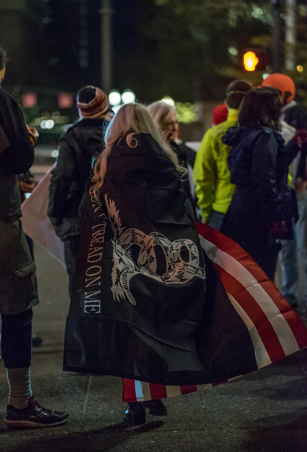 "A Patriot Prayer protest attendee wears the American flag and another, which reads, ""Don't tread on me,"" draped across her shoulders. The alt-right group Patriot Prayer protested Hillary Clinton's Portland speaking engagement outside the Arlene Schnitzer Concert Hall on Tuesday, December 12. Their demonstration was met with a counter-protest by Antifa, and the two groups traded insults and jeers across SW Main Street from 6:00 p.m. until the event's conclusion at approximately 9:30 p.m. Throughout the evening, both Patriot Prayer and Antifa sporadically marched around the theater. At least one scuffle occurred during one such march. Photo by Kit MacAvoy, Oregon News Lab"