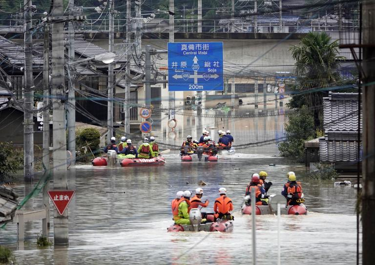 Rescuers on boats head for search in the partly submerged area in water after heavy rain in Kurashiki city, Okayama prefecture, southwestern Japan, Sunday, July 8, 2018. Heavy rainfall hammered southern Japan for the third day, prompting new disaster warnings on Kyushu and Shikoku islands Sunday. (Koji Harada/Kyodo News via AP)