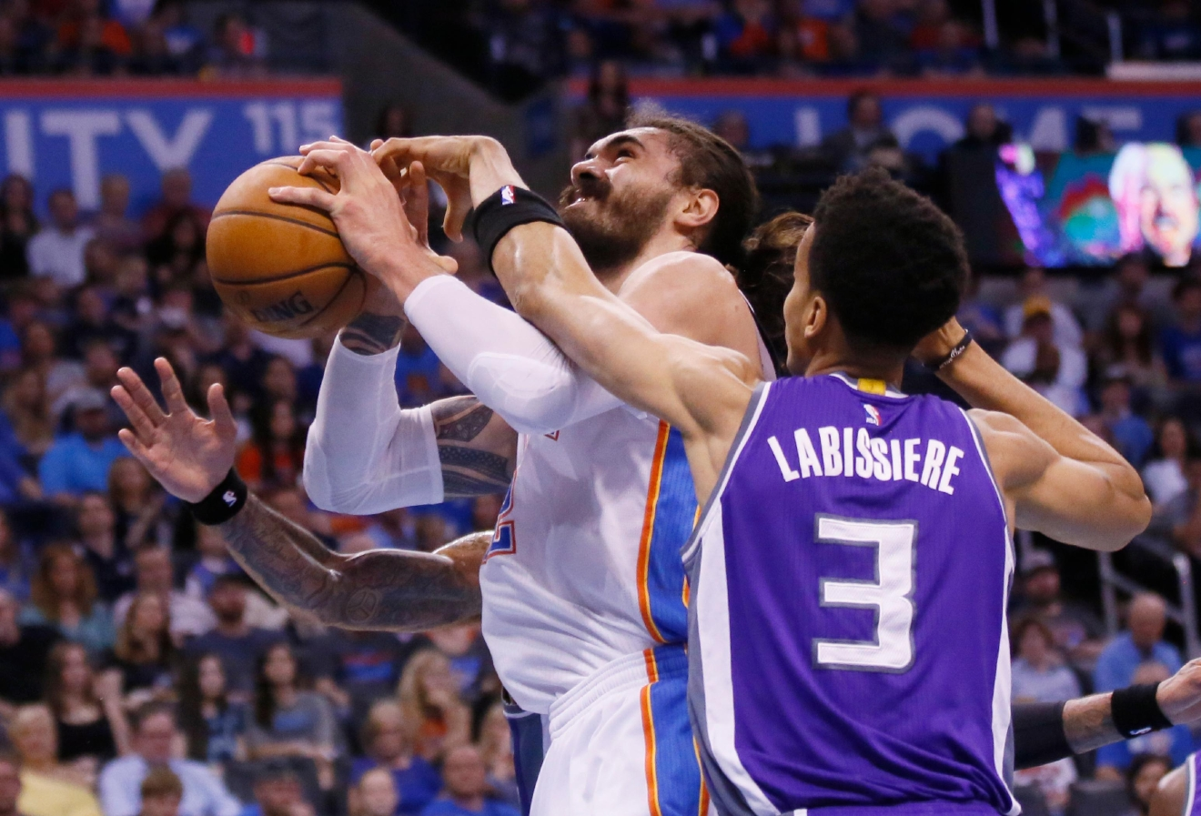 Oklahoma City Thunder center Steven Adams, left, is fouled by Sacramento Kings forward Skal Labissiere (3) in the first quarter of an NBA basketball game in Oklahoma City, Saturday, March 18, 2017. (AP Photo/Sue Ogrocki)