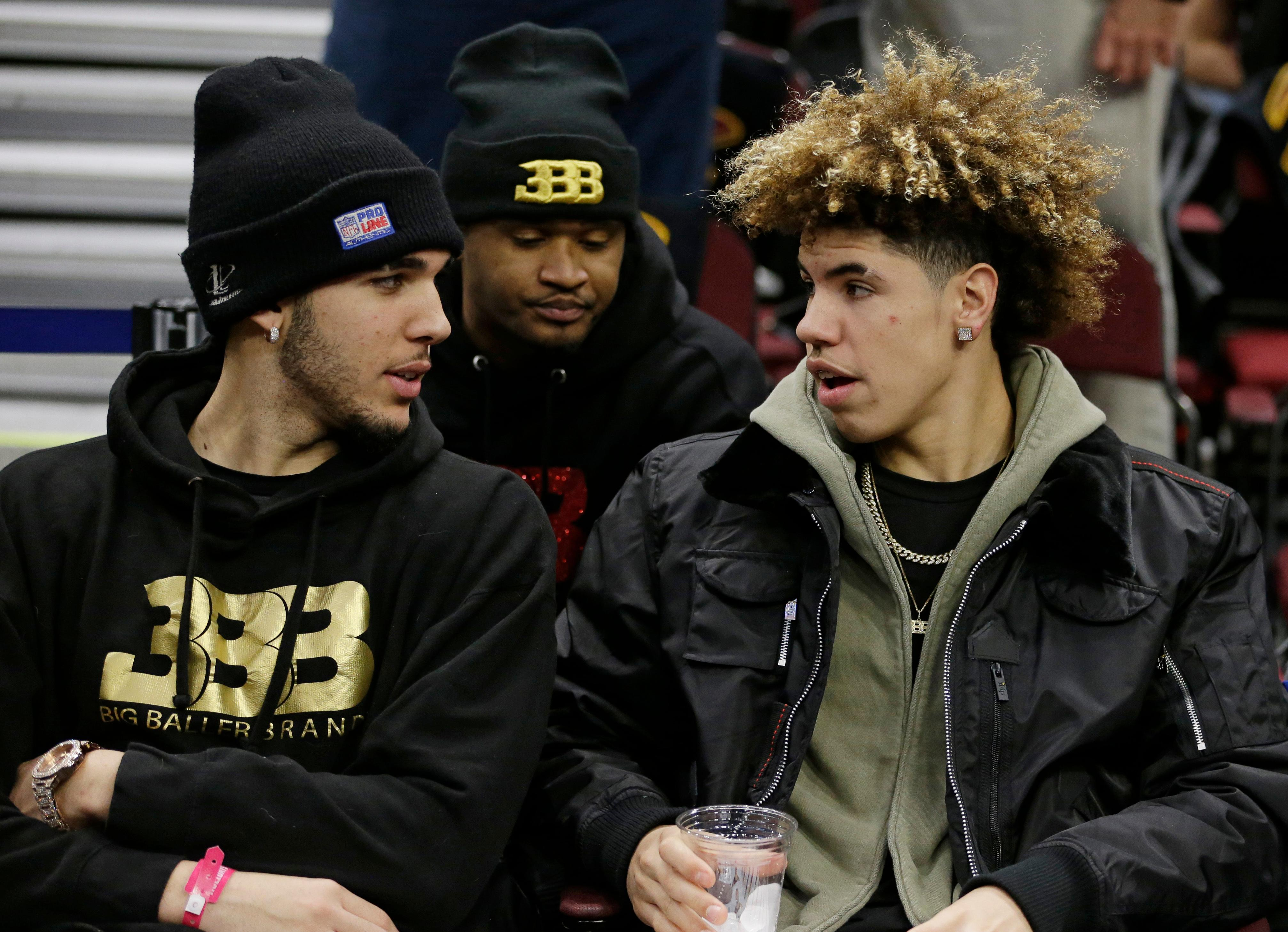 LiAngelo Ball, left, and his brother, LaMelo, talk before an NBA basketball game between the Los Angeles Lakers and the Cleveland Cavaliers, Thursday, Dec. 14, 2017, in Cleveland. (AP Photo/Tony Dejak)
