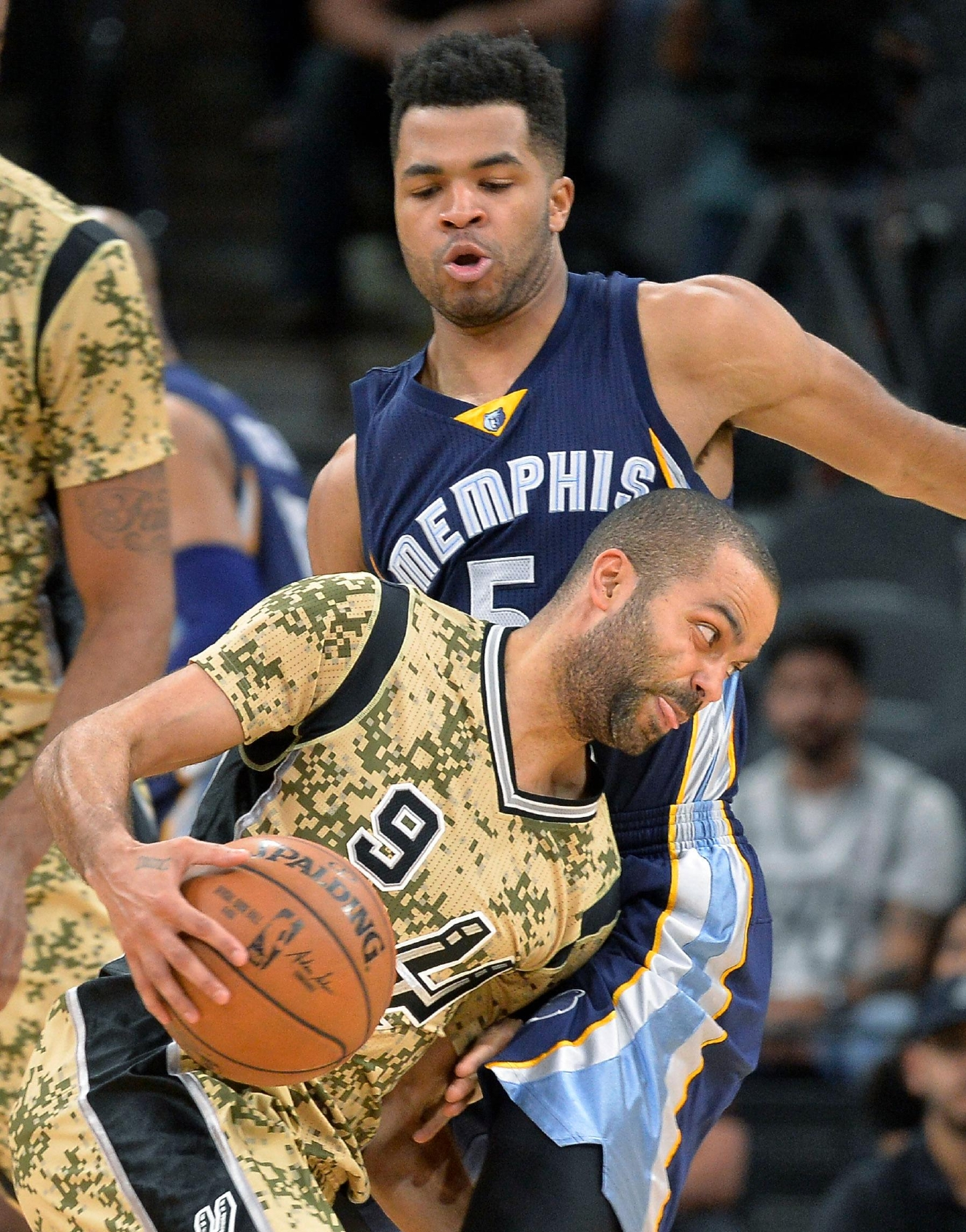 San Antonio Spurs guard Tony Parker (9), of France, drives around Memphis Grizzlies guard Andrew Harrison during the first half of an NBA basketball game, Thursday, March 23, 2017, in San Antonio. (AP Photo/Darren Abate)