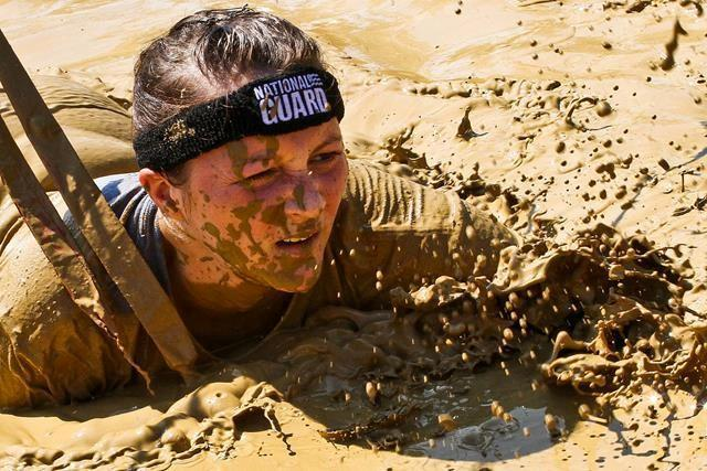 Army 2nd Lt. Mary Kauffman crawls through mud during the Warrior Dash 5k mud run in North Lawrence, Ohio, Aug. 11, 2013. Kauffman and 19 other Ohio National Guardsman participated in the event to promote recruiting and retention.