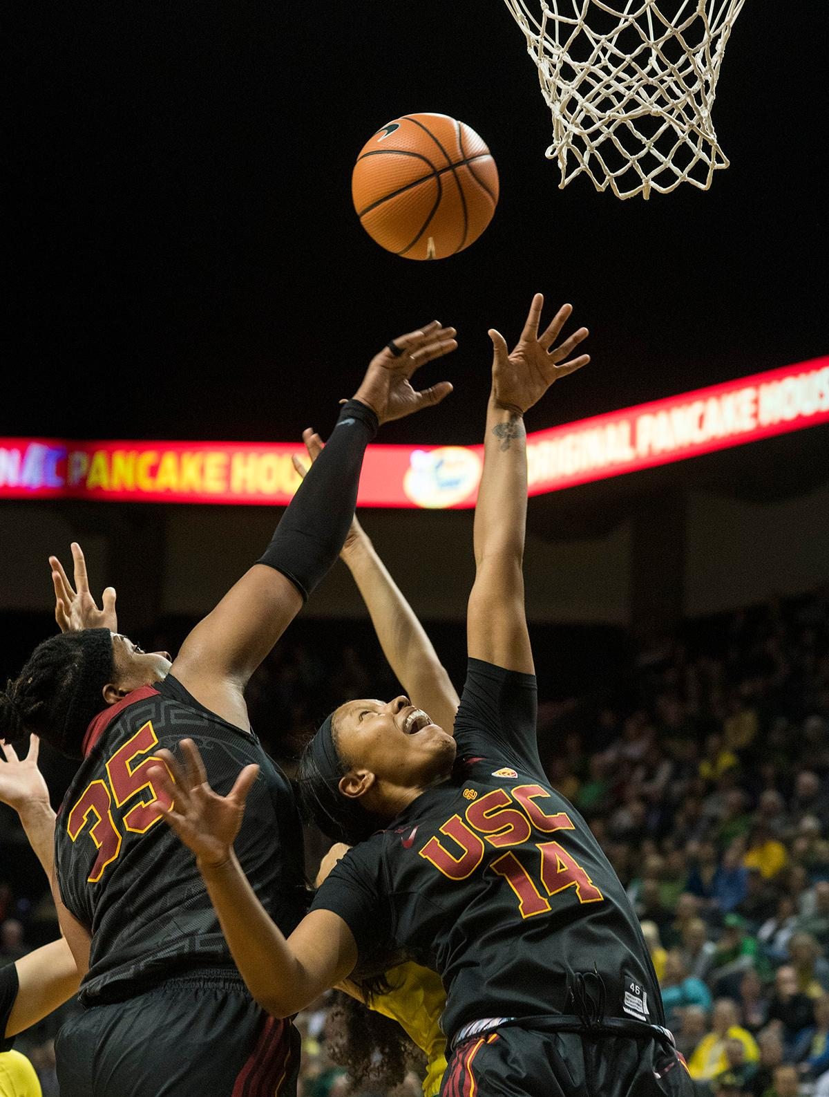 USC Trojans Kristen Simon (#35) and Sadie Edwards (#14) attempt to get the rebound. The Oregon Ducks defeated the USC Trojans 80-74 on Friday at Matthew Knight Arena in a game that went into double overtime. Lexi Bando sealed the Ducks' victory by scoring a three-pointer in the closing of the game. Ruthy Hebard set a new NCAA record of 30 consecutive field goals in three straight games, the old record being 28. Ruthy Hebard got a double-double with 27 points and 10 rebounds, Mallory McGwire also had 10 rebounds. The Ducks had four players in double digits. The Ducks are now 24-4, 13-2 in the Pac-12, and are tied for first with Stanford. Photo By Rhianna Gelhart, Oregon News Lab