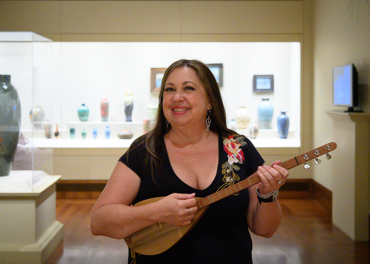 Dawn Larsen, Fringe performer, strums a tune in the Cincinnati gallery at the Art Museum. / Image: Cincinnati Refined // Published: 6.1.19