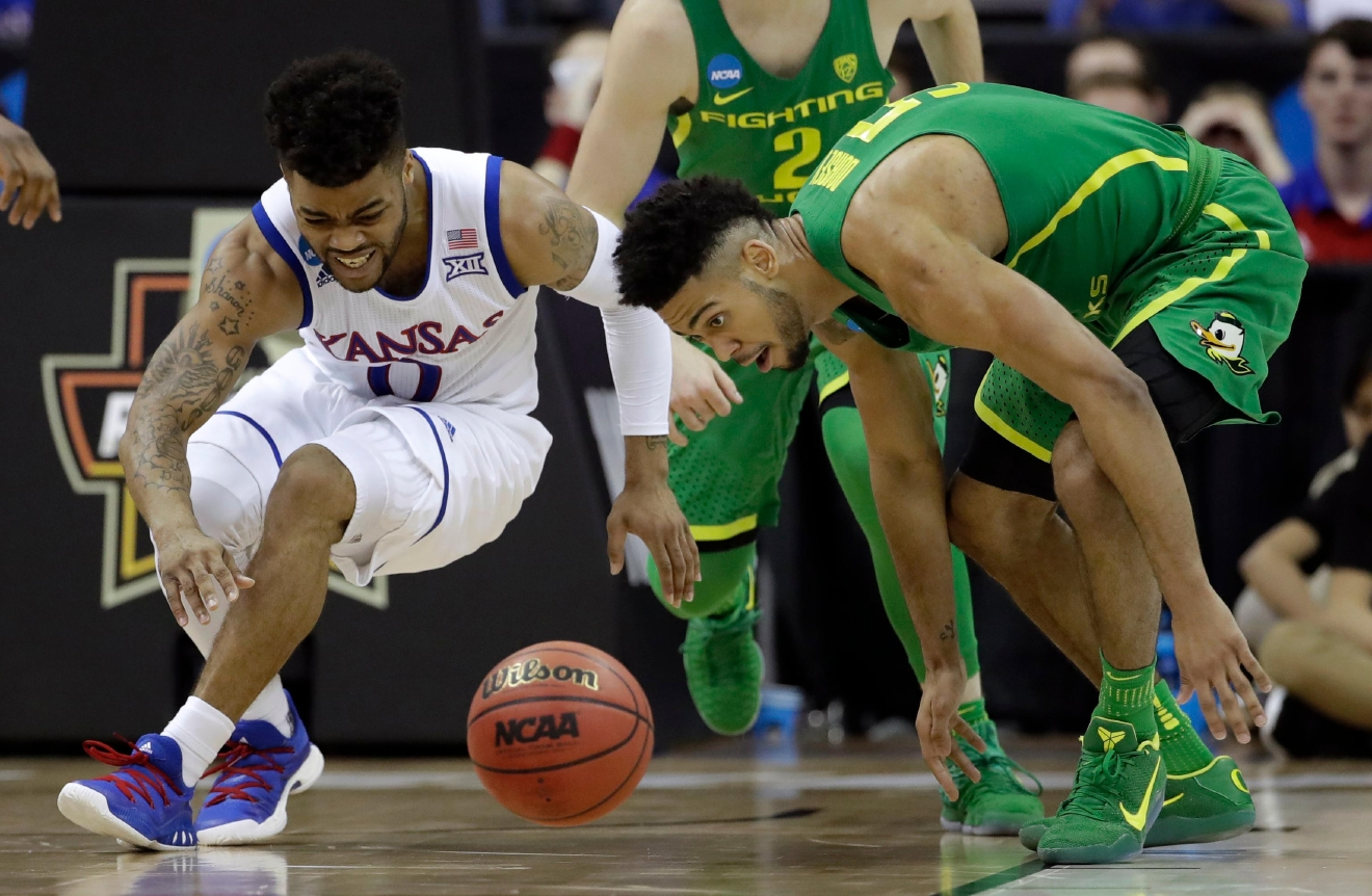Kansas guard Frank Mason III, left, and Oregon guard Tyler Dorsey watch a loose ball during the second half of the Midwest Regional final of the NCAA men's college basketball tournament, Saturday, March 25, 2017, in Kansas City, Mo. (AP Photo/Charlie Riedel)