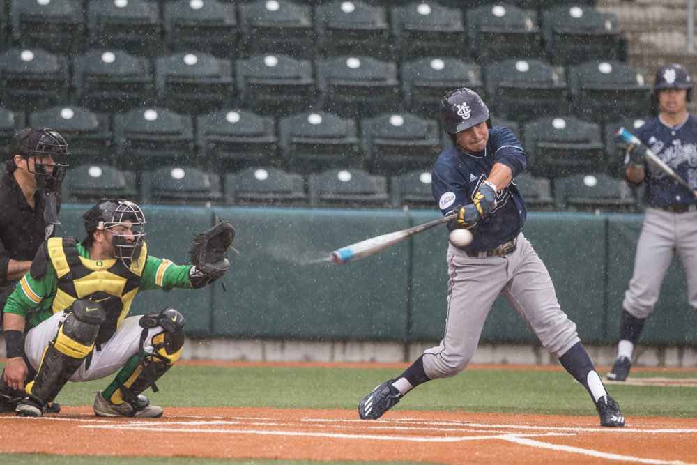 UC Irvine Anteaters infielder Mikey Duarte (#1) swings on a pitch during a brief downpour. Oregon Ducks pitcher Matt Mercer (#11) throws a pitch.  In the second of the three game series, the Ducks beat the UC Irvine Anteaters 6-3. Photo by Austin Hicks, Oregon News Lab