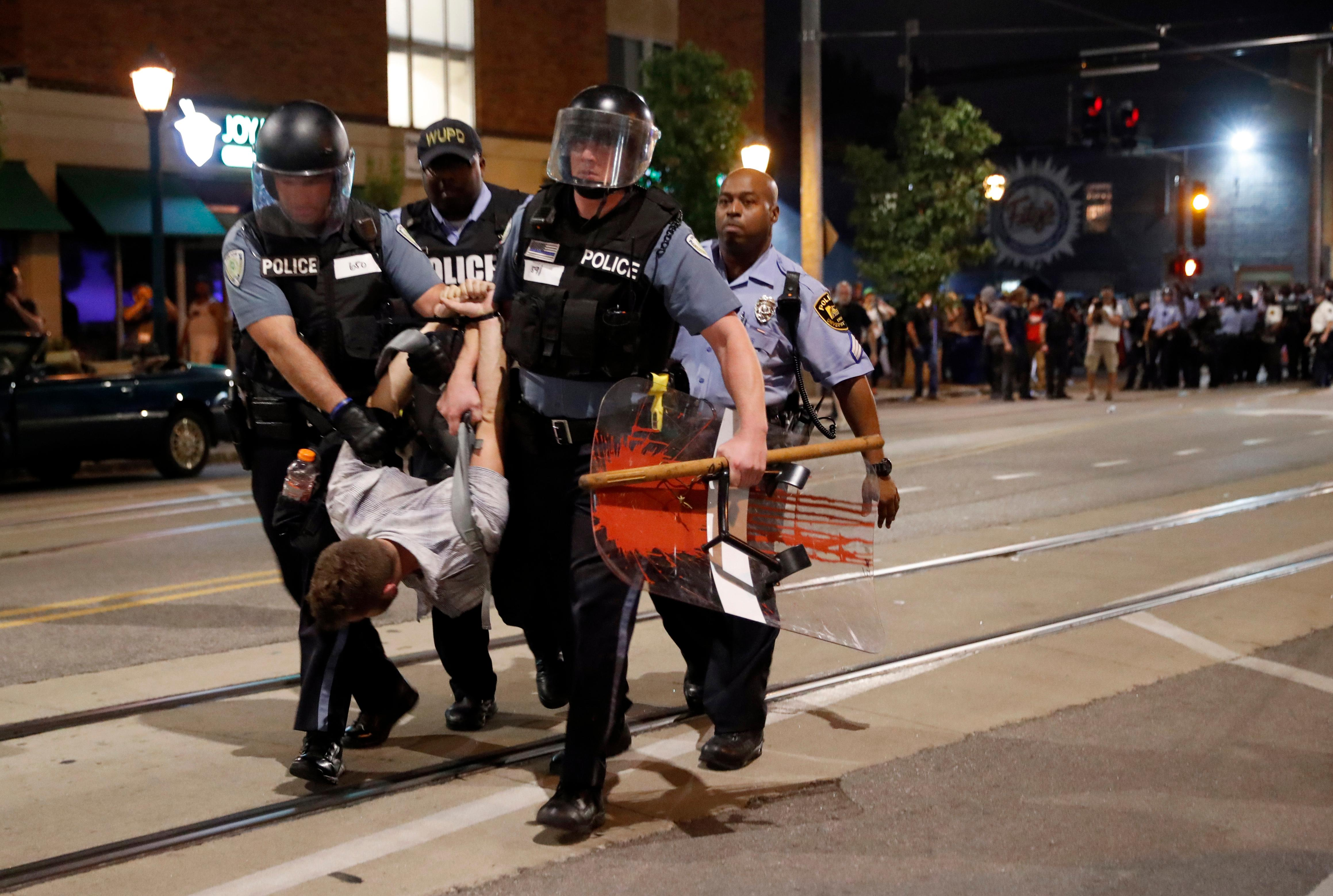 Police arrest a man as they try to clear a violent crowd Saturday, Sept. 16, 2017, in University City, Mo. Earlier, protesters marched peacefully in response to a not guilty verdict in the trial of former St. Louis police officer Jason Stockley. (AP Photo/Jeff Roberson)