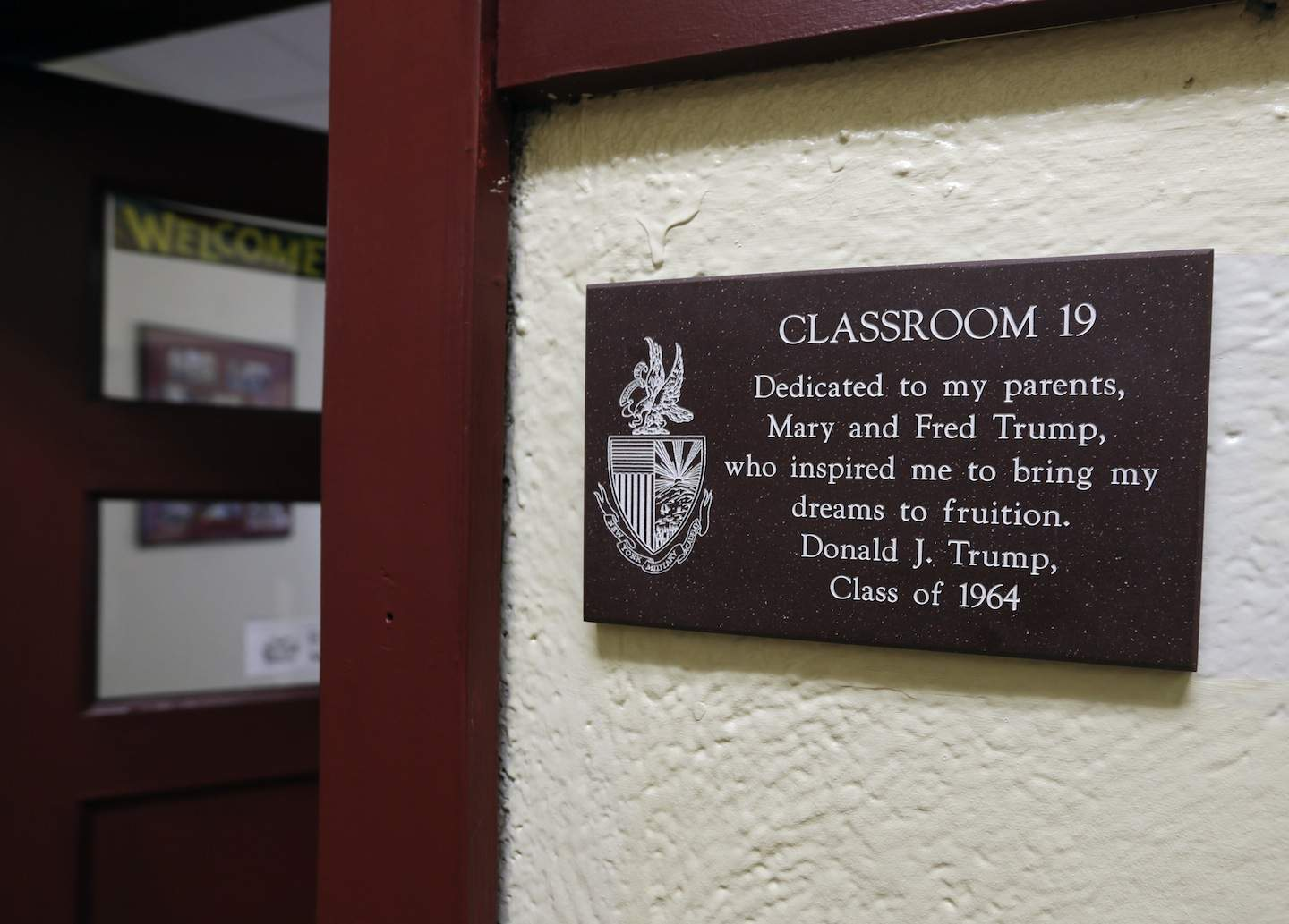 In this Thursday, Sept. 8, 2016 photo, a plaque with a dedication to Donald Trump's parents, Mary and Fred Trump, hangs outside a classroom at the New York Military Academy in Cornwall-on-Hudson, N.Y. While Republican presidential nominee, Trump, talks tough about dealing with China, his old military prep school is building bridges to that country. The New York Military Academy began classes this fall with new Chinese backing and a former New York City high school principal originally from China in charge. (AP Photo/Mike Groll)