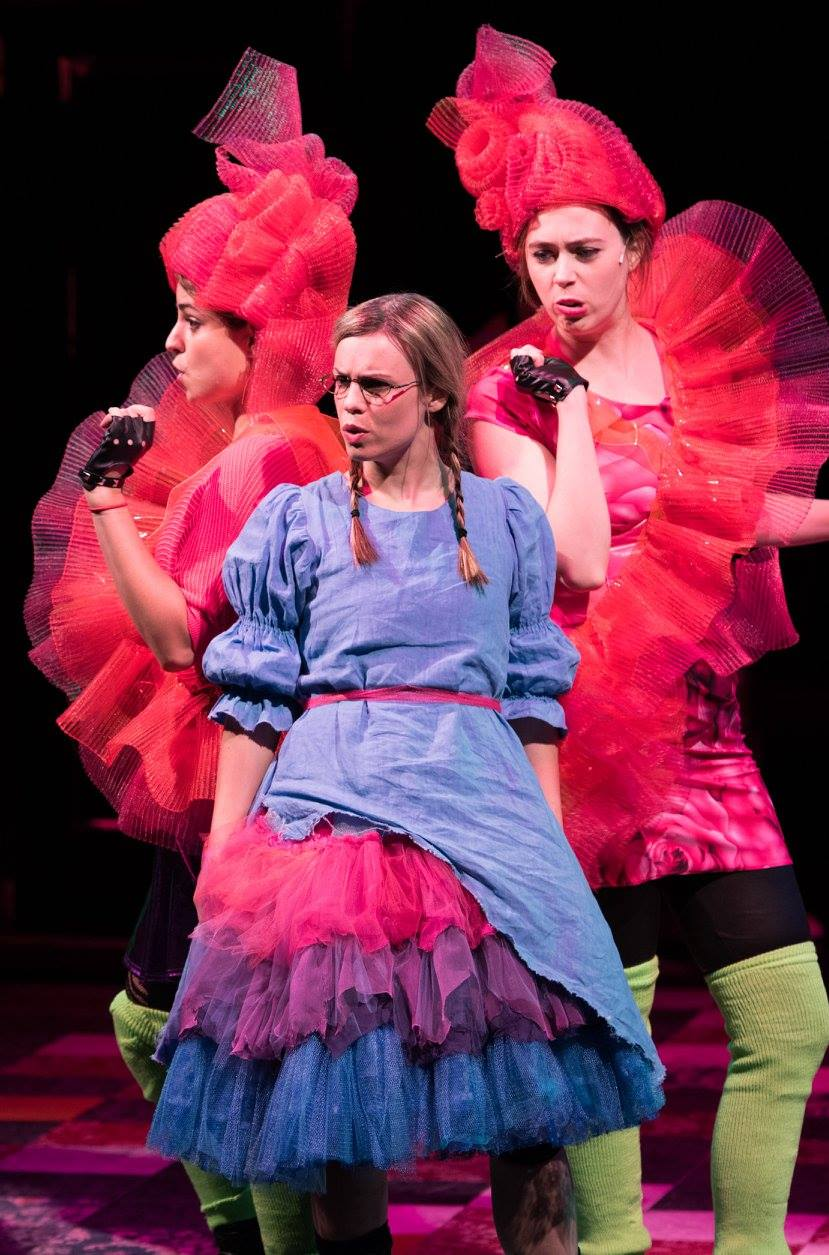 "Alice and the Roses have a sing-off debating whether it is best to be or not to be a ""red, red rose"". (L-R: Daven Ralston, Erin Weaver, Tess Higgins) Wonderland: Alice's Rock and Roll Adventure, Imagination Stage.  (Image: Margot Schulman)"
