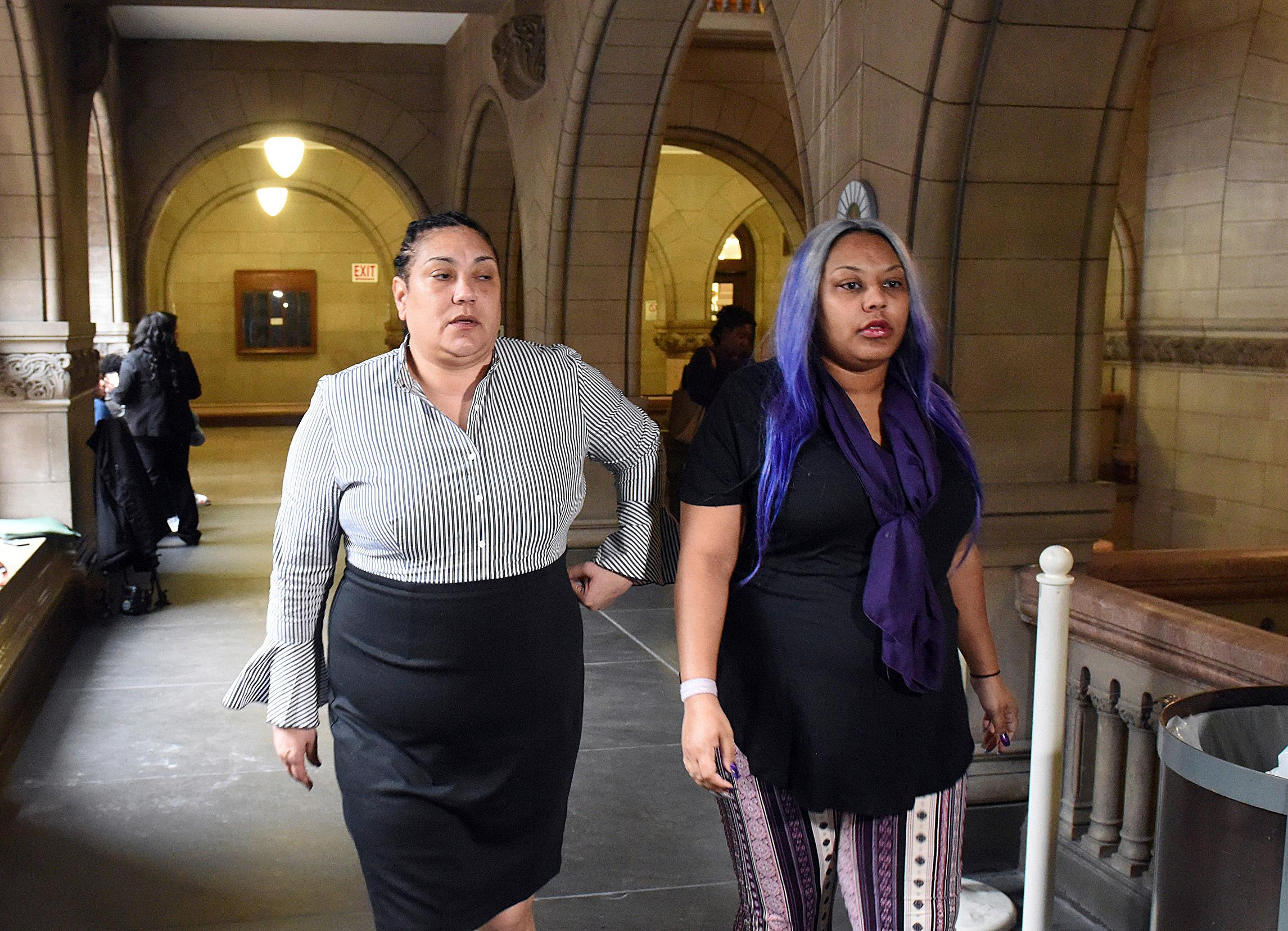 Michelle Kenney, left, mother of Antwon Rose II, and her daughter, Kyra Jamison, make their way back to the courtroom at the Allegheny County Courthouse in Pittsburgh on Thursday, March 21, 2019.{ } (Darrell Sapp/Pittsburgh Post-Gazette via AP, Pool)