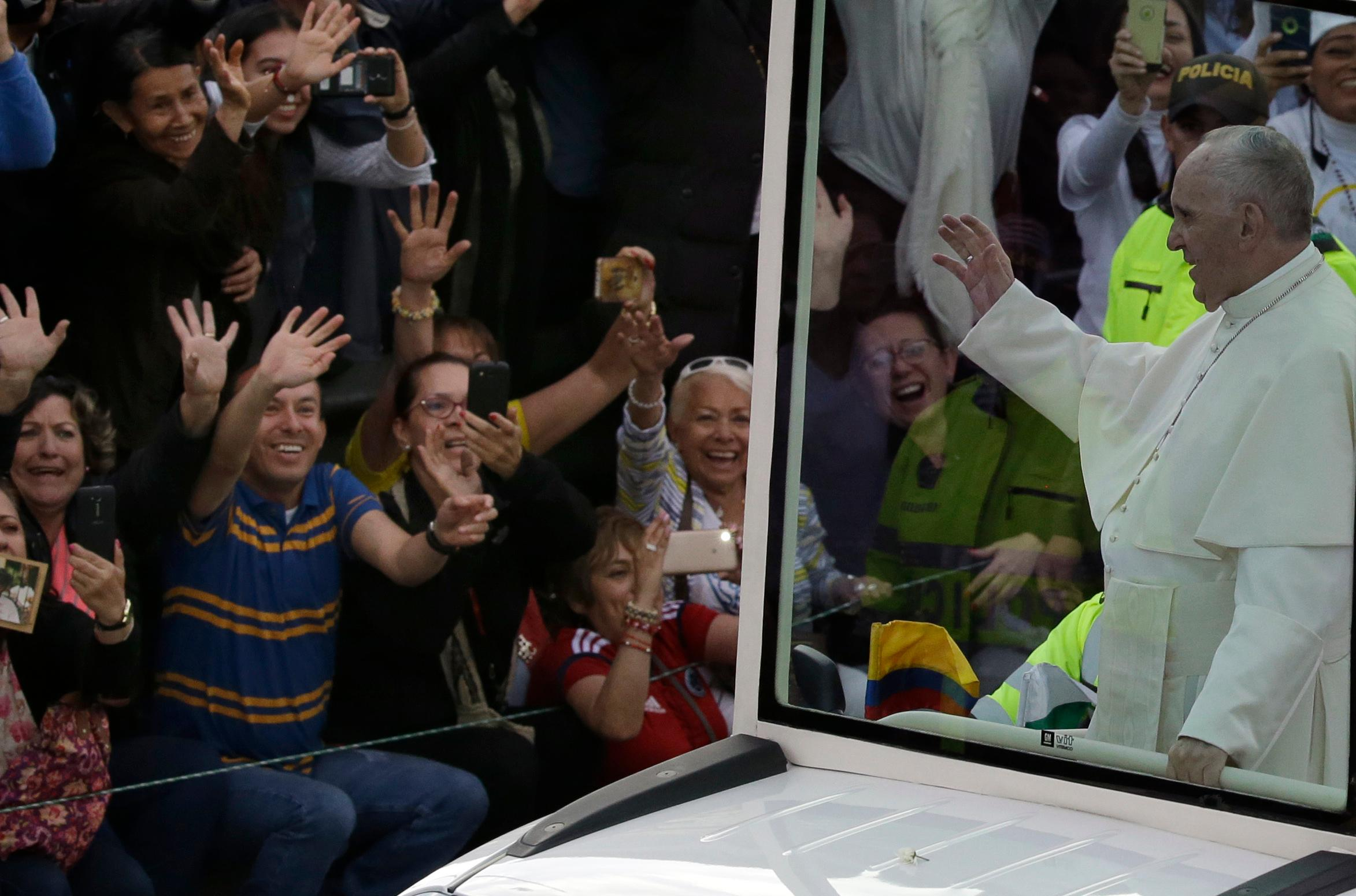 People greet Pope Francis passing by in his popemobile as he makes his way from the airport to the Nunciatura, after arriving to Bogota, Colombia, Wednesday, Sept. 6, 2017. Pope Francis has arrived in Colombia for a five-day visit. (AP Photo/Fernando Vergara)