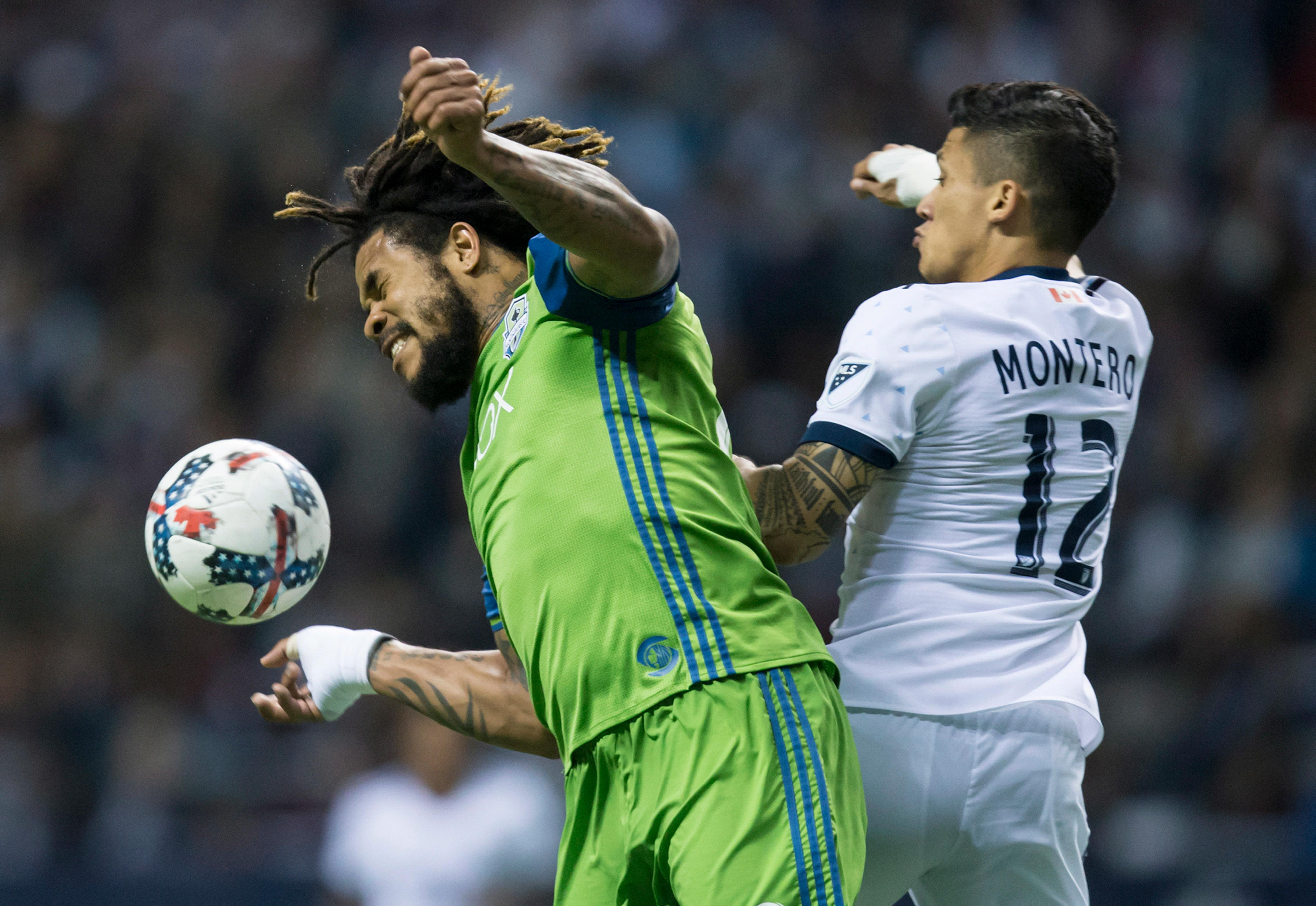 Seattle Sounders' Roman Torres, left, prevents a pass from getting to Vancouver Whitecaps' Fredy Montero during the second half of an MLS playoff soccer match in Vancouver, British Columbia, Sunday, Oct. 29, 2017. (Darryl Dyck/The Canadian Press via AP)