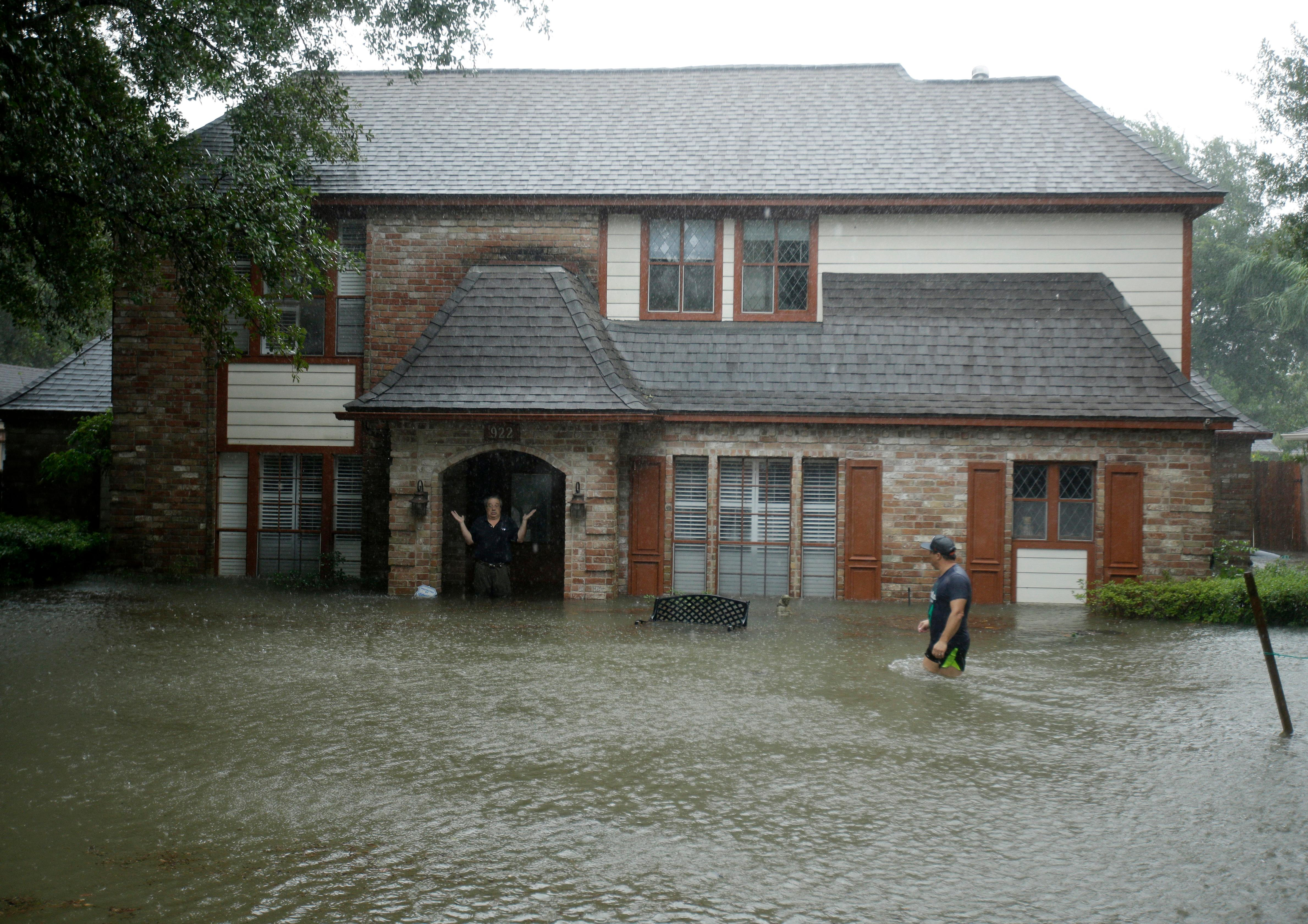 A man standing in the doorway of his flooded home responds to an evacuation offer in a neighborhood inundated by floodwaters from Tropical Storm Harvey on Monday, Aug. 28, 2017, in Houston, Texas. (AP Photo/Charlie Riedel)