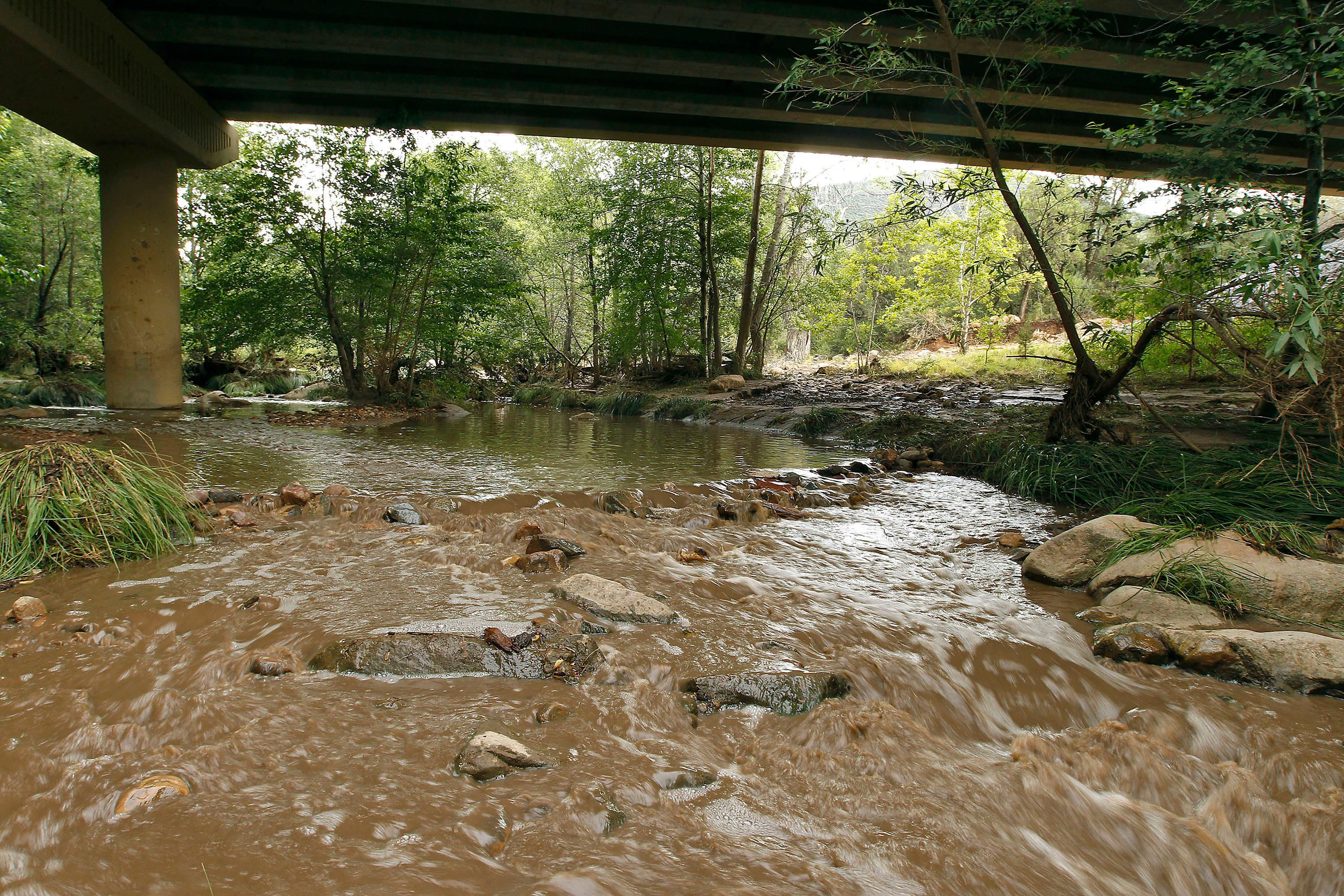 Muddy floodwaters of the East Verde River flow under a bridge where one victim of the flash flood was found during a search and rescue operation by the Gila County Sheriff's Office on Sunday, July 16, 2017, in Payson, Ariz. Search and rescue crews, including 40 people on foot and others in a helicopter, have recovered bodies of children and adults, some as far as two miles down the river after Saturday's flash flooding poured over a popular swimming area inside the Tonto National Forest in central Arizona. (AP Photo/Ralph Freso)