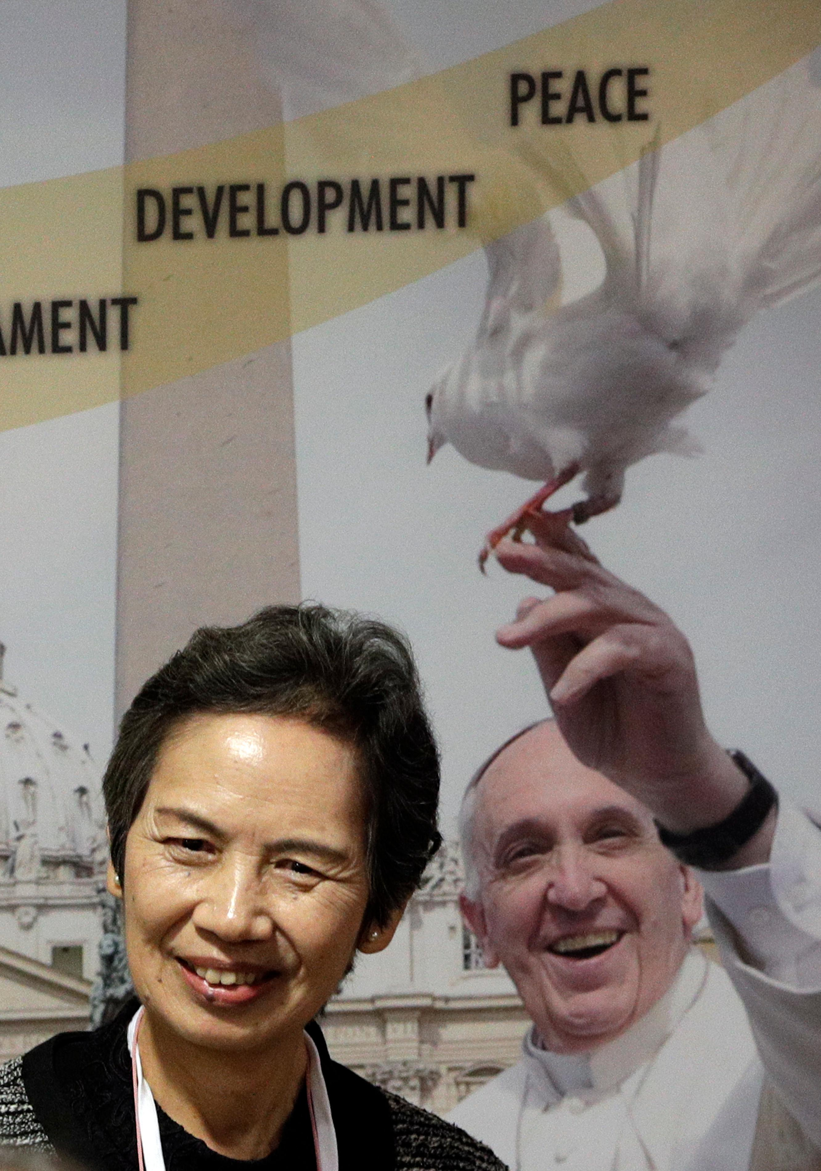 Assitant Secretary General Nihon Hidankyo and atomic bomb survivor Masako Wada smiles in front of a poster showing Pope Francis as she attends a conference on nuclear disarmament, at the Vatican, Friday, Nov. 10, 2017. The Vatican hosted Nobel laureates, U.N. and NATO officials and a handful of nuclear powers at a conference aimed at galvanizing support for a global shift from the Cold War era policy of nuclear deterrence to one of total nuclear disarmament. (AP Photo/Andrew Medichini)