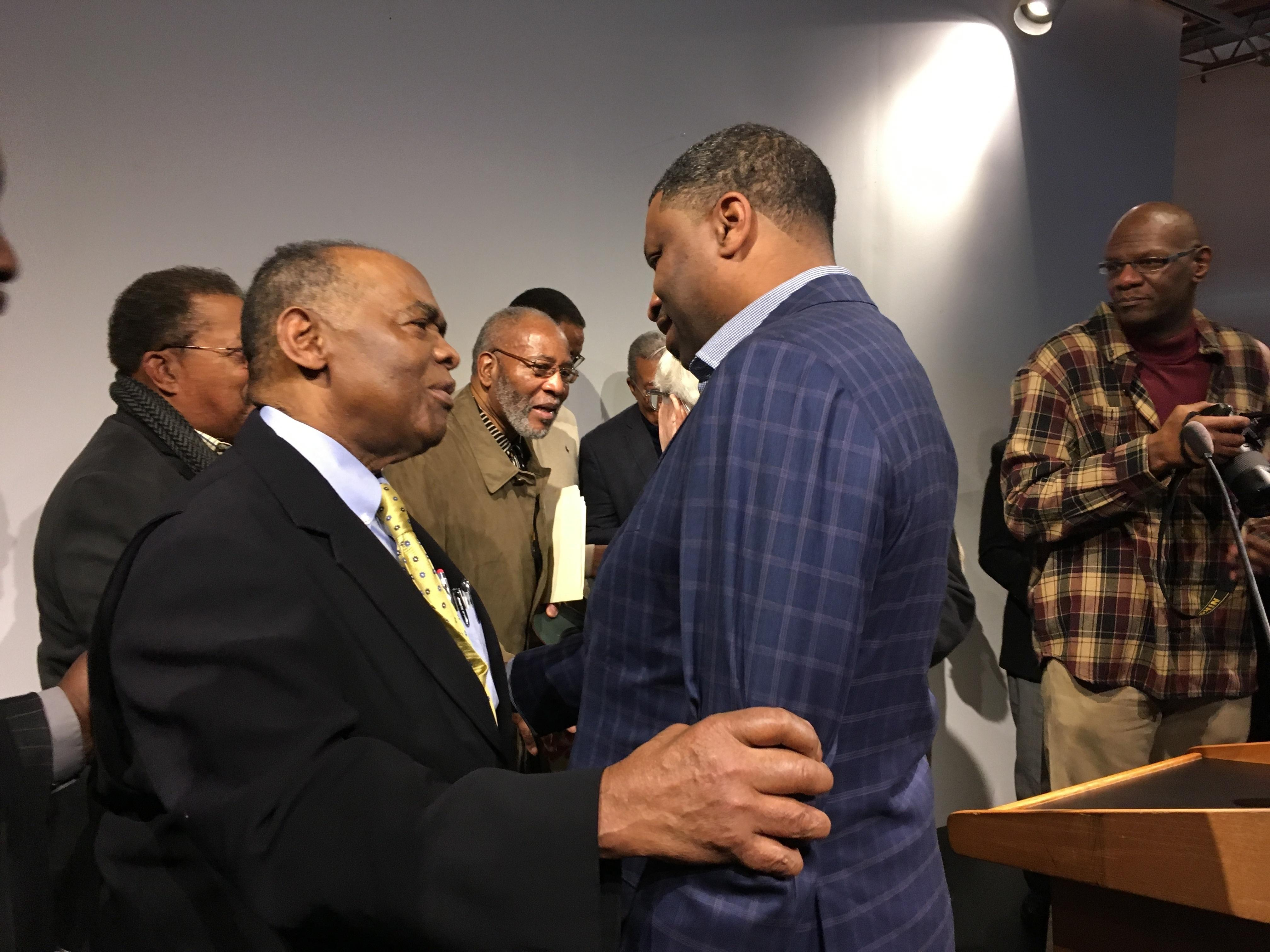 NAACP President Derrick Johnson, right, speaks with Dr. Robert Smith, former president of the Medical Committee for Human Rights, after a speech Saturday, Dec. 9, 2017, denouncing the visit of President Donald Trump in Jackson, Miss., for the opening of twin history and civil rights museums marking Mississippi's bicentennial. (AP Photo/Jeff Amy)