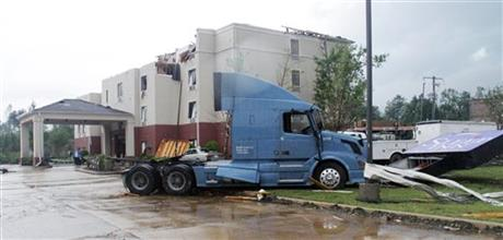 A semi tractor sits on top of the sign of the Sleep Inn located on North Gloster Street in Tupelo, Miss, after a tornado touched down on Monday, April 28, 2014.(AP Photo/Jim Lytle)