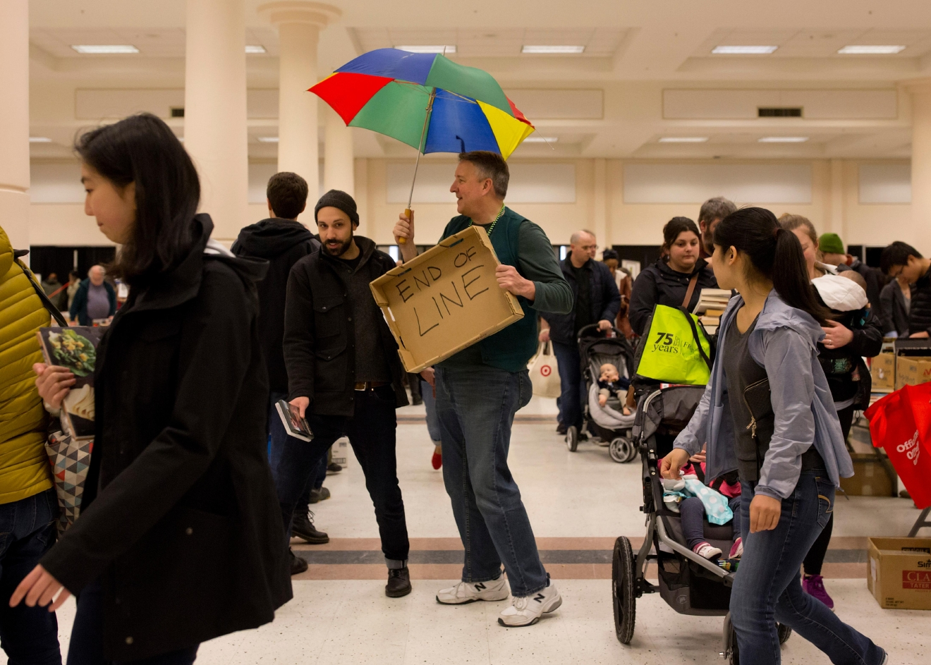 Steve Fawthrop, a board member of the Friends of Seattle Public Libraries, marks the end of the checkout line with a colorful umbrella during the Big Book Sale 2017, hosted by the Friends of Seattle Public LIbraries. (Sy Bean / Seattle Refined)