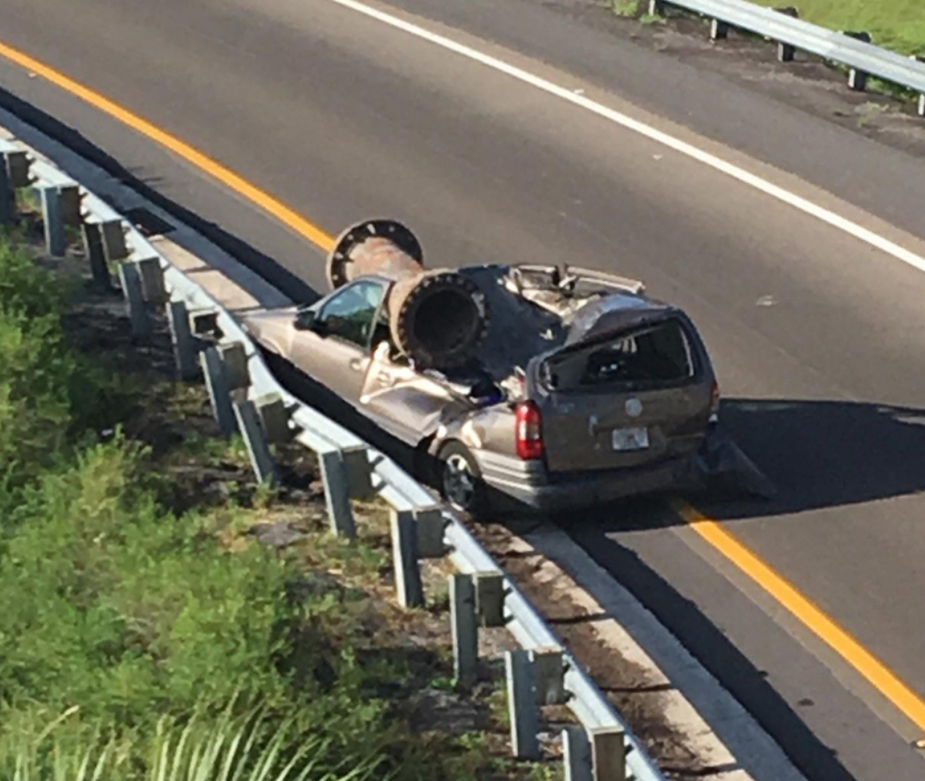 In this photo provided by the Florida Highway Patrol, a van is shown with a piece of scrap metal on its roof in Orange County, Florida, on Saturday, July 15, 2017. The highway patrol said the scrap metal fell from a truck that had lost control and overturned on an overpass. The van driver and the driver of the semi had only minor injuries. (Florida Highway Patrol via AP)