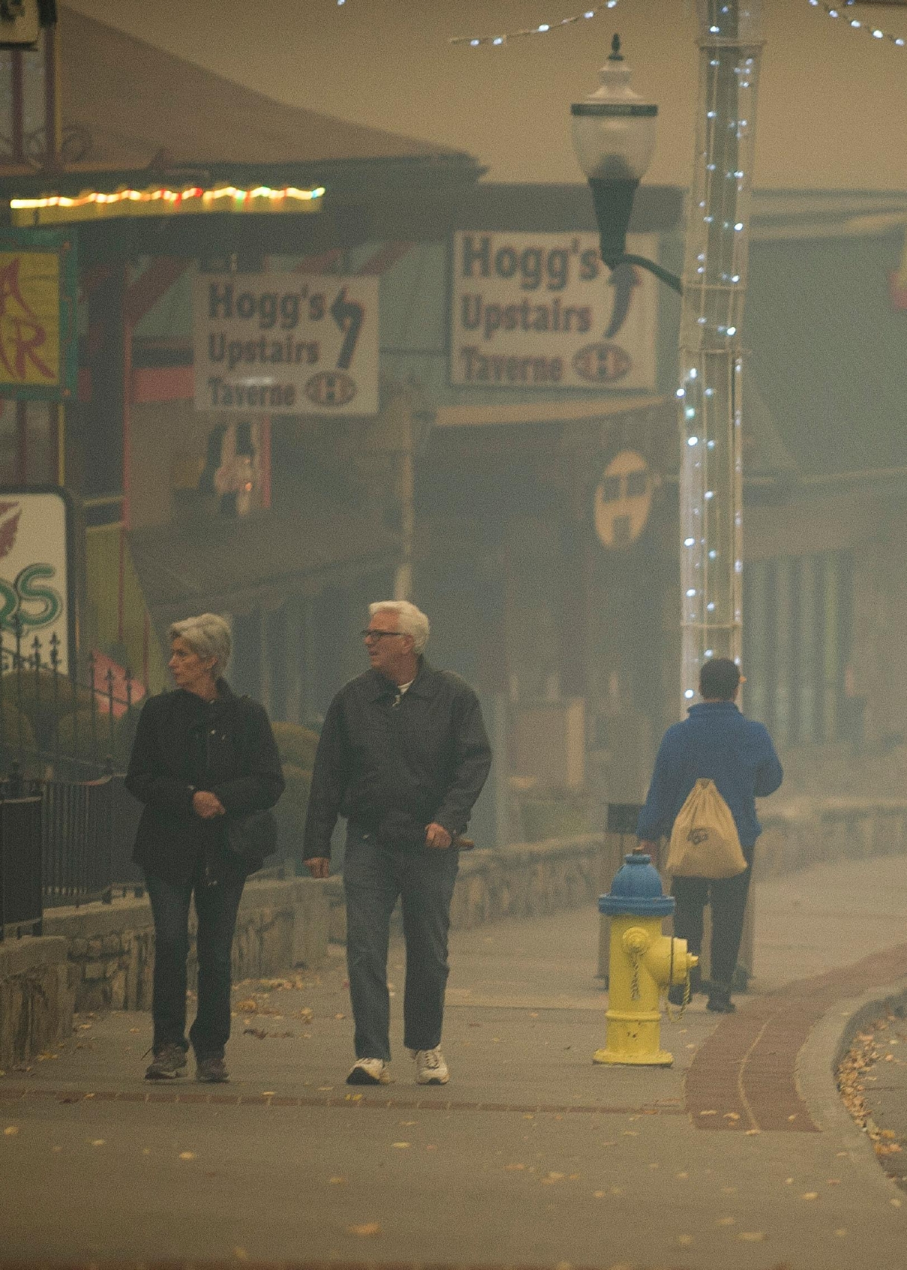 Thick smoke from area forest fires looms as people walk in Gatlinburg, Tenn., Monday, Nov. 28, 2016. Gatlinburg officials say several areas are being evacuated as a result of fires in and around Great Smoky Mountains National Park. (Brianna Paciorka/Knoxville News Sentinel via AP)