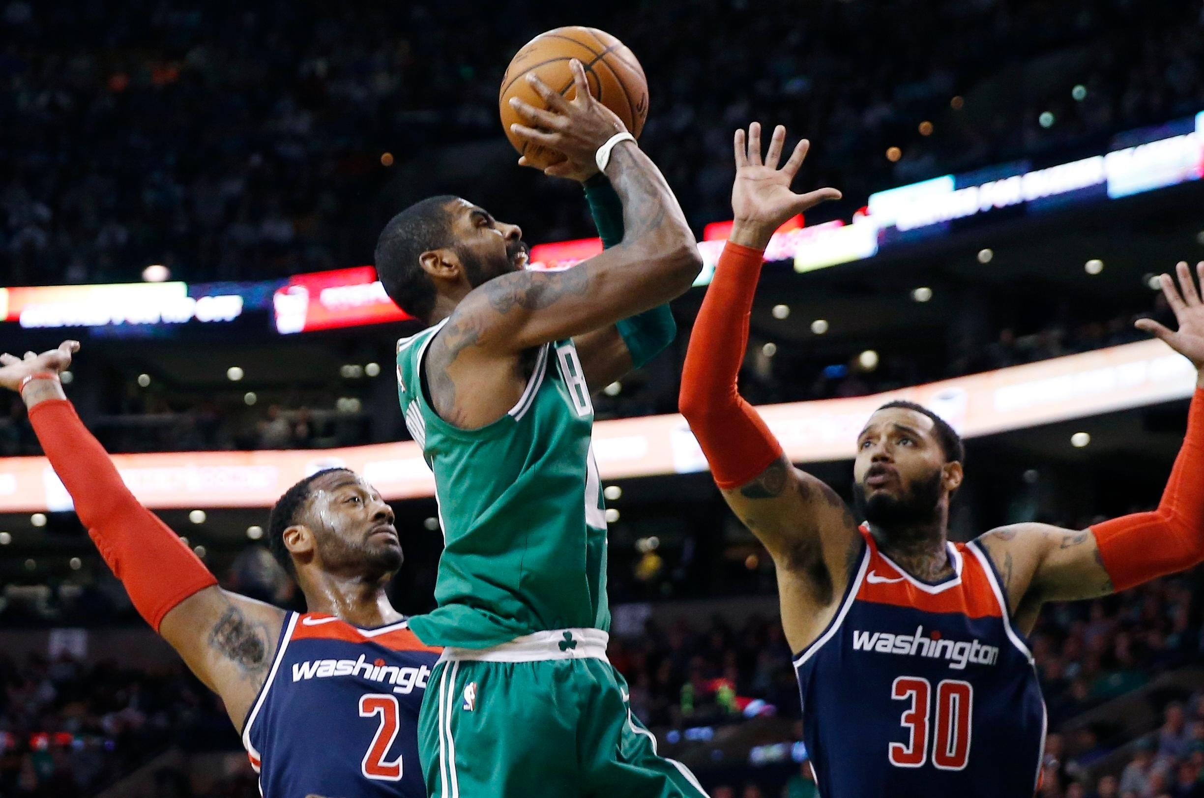 Boston Celtics' Kyrie Irving, center, shoots between Washington Wizards' John Wall (2) and Mike Scott (30) during the first quarter of an NBA basketball game in Boston, Monday, Dec. 25, 2017. (AP Photo/Michael Dwyer)