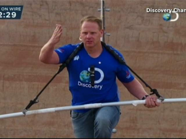 Nik Wallenda is almost there as he takes his right hand off the bar briefly.