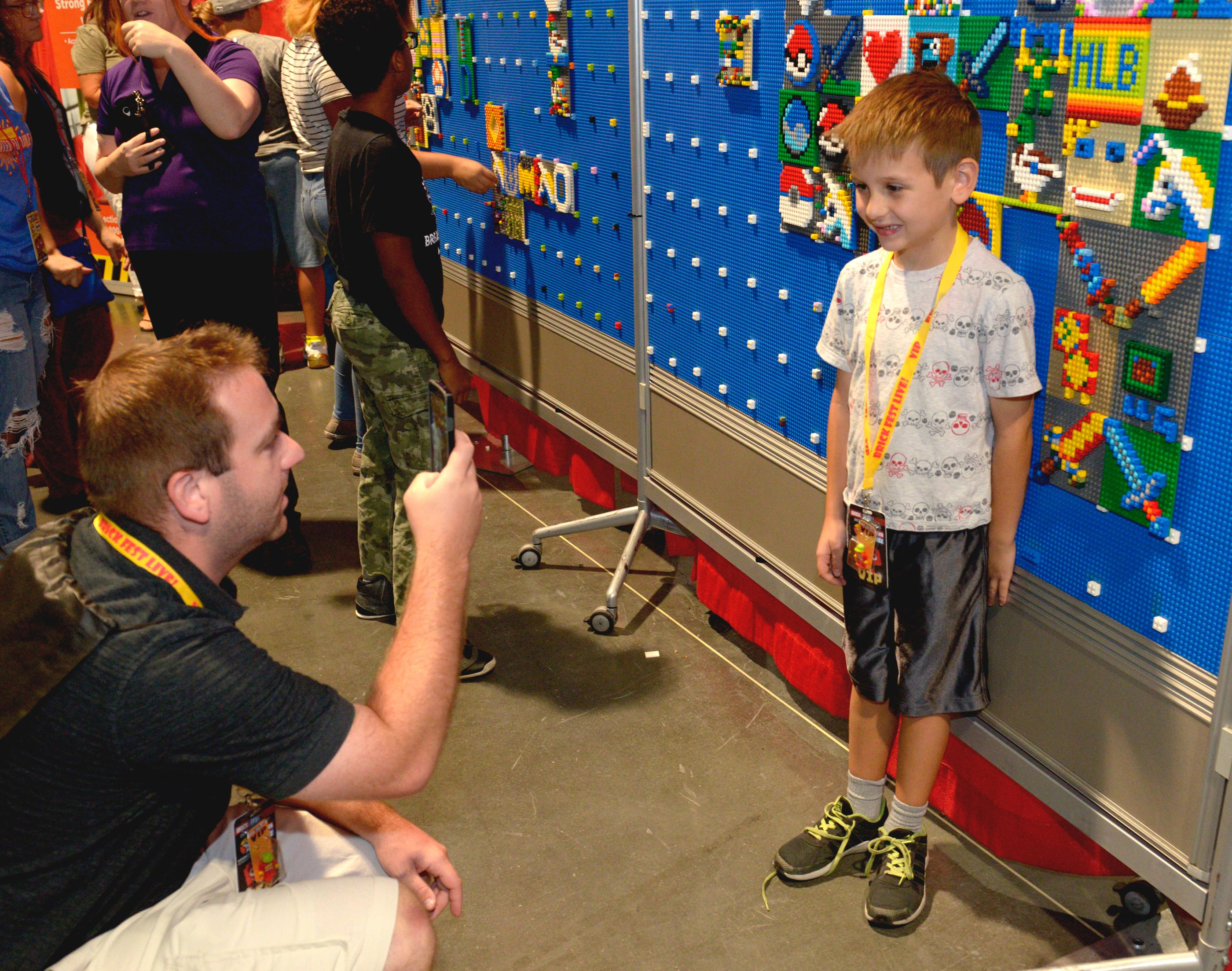 Dad takes a photo as they put their dueling sword mosaics on the Mosaic Wall during the Brick Fest Live Lego Fan Experience at the Las Vegas Convention Center, September 9, 2017. [Glenn Pinkerton/Las Vegas News Bureau]