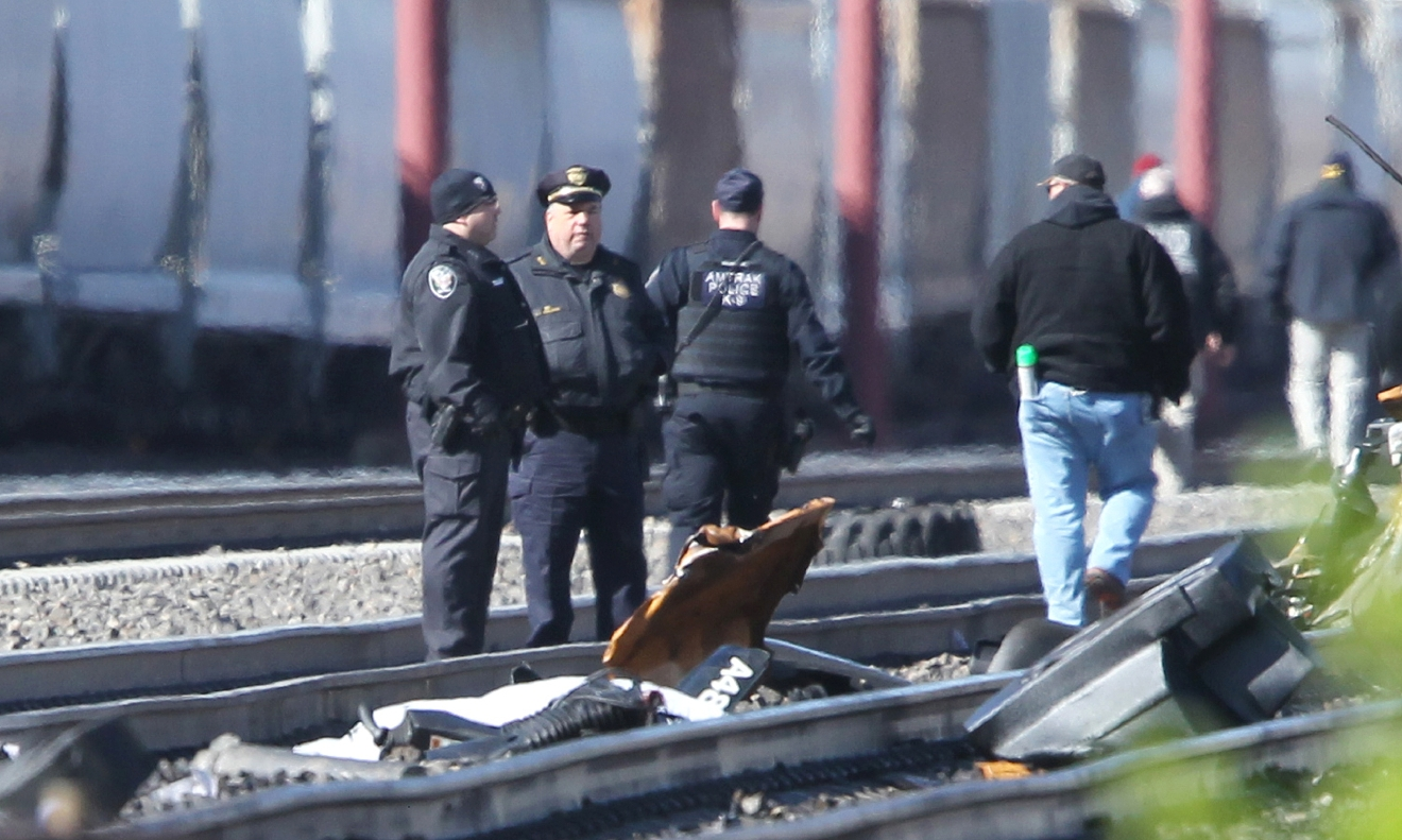 Emergency personnel stand by debris from a deadly train crash in Chester, Pa., Sunday, April 3 2016. The Amtrak train struck a piece of construction equipment just south of Philadelphia causing a derailment. (Michael Bryant/The Philadelphia Inquirer via AP)  PHIX OUT; TV OUT; MAGS OUT; NEWARK OUT; MANDATORY CREDIT