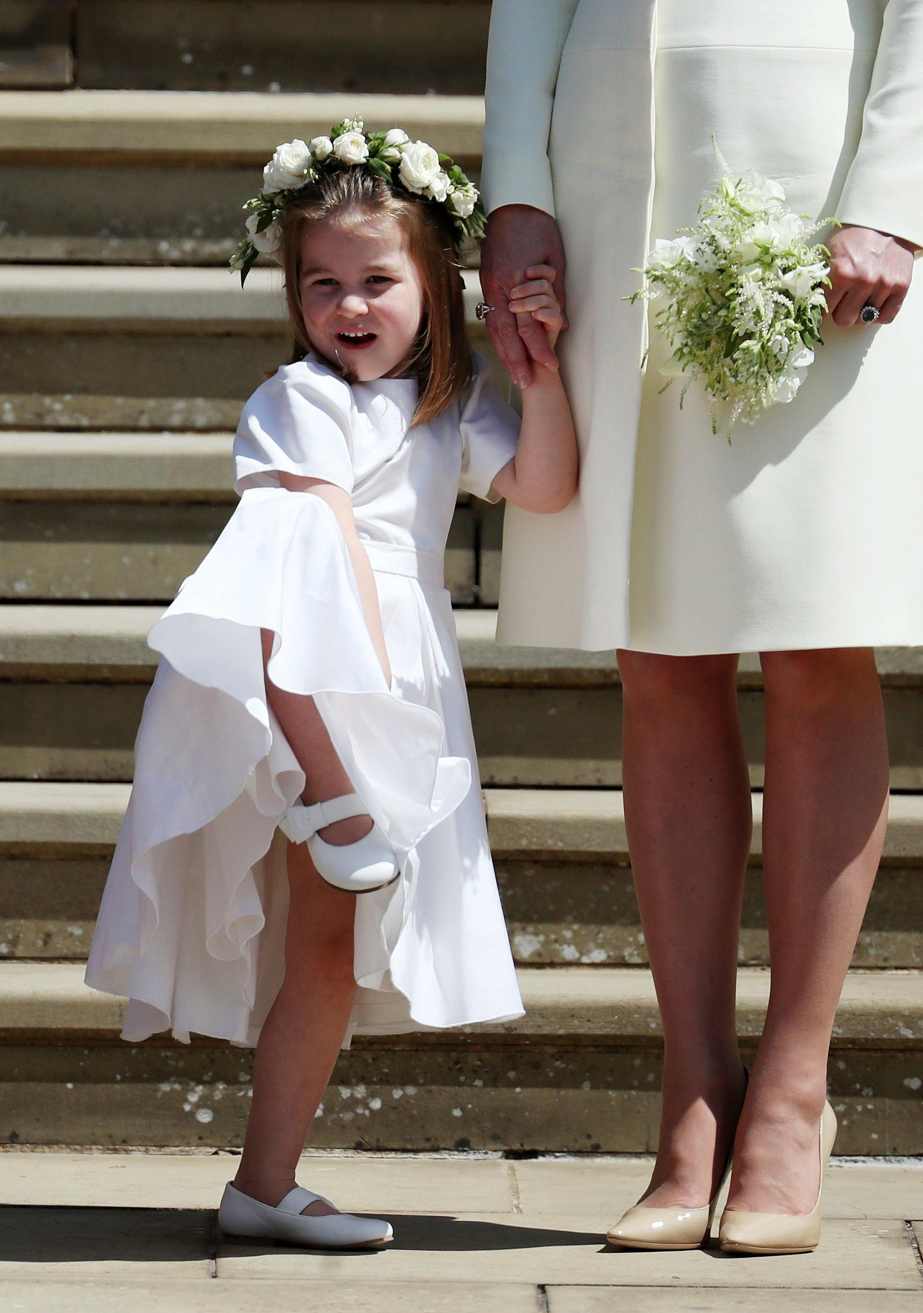 Princess Charlotte looks at Meghan Markle and Britain's Prince Harry on the steps of St George's Chapel at Windsor Castle following their wedding in Windsor, near London, England, Saturday, May 19, 2018. (Jane Barlow/pool photo via AP)