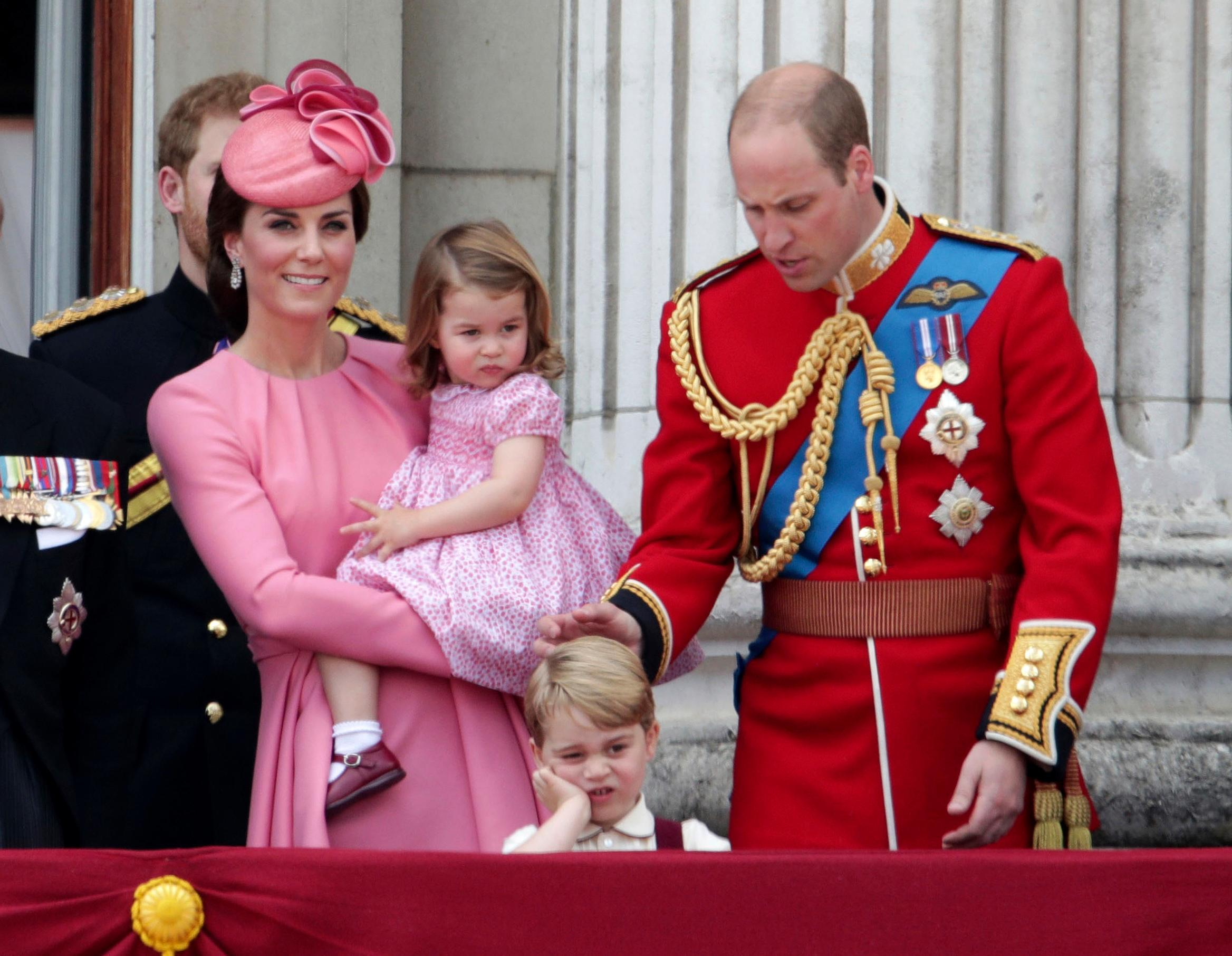 Kate, The Duchess of Cambridge, holds Princess Charlotte with Prince William at right and Prince George, foreground, on the balcony of Buckingham Palace, after attending the annual Trooping the Colour Ceremony in London, Saturday, June 17, 2017. (Yui Mok/PA via AP)