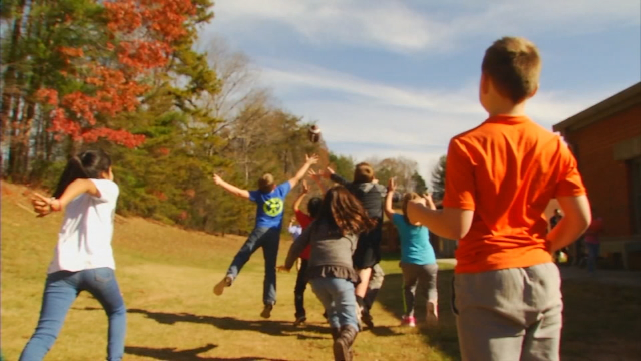 West Swain Elementary teacher Chris Rogers throws and catches a football with his students during recess. (Photo credit: WLOS Staff)