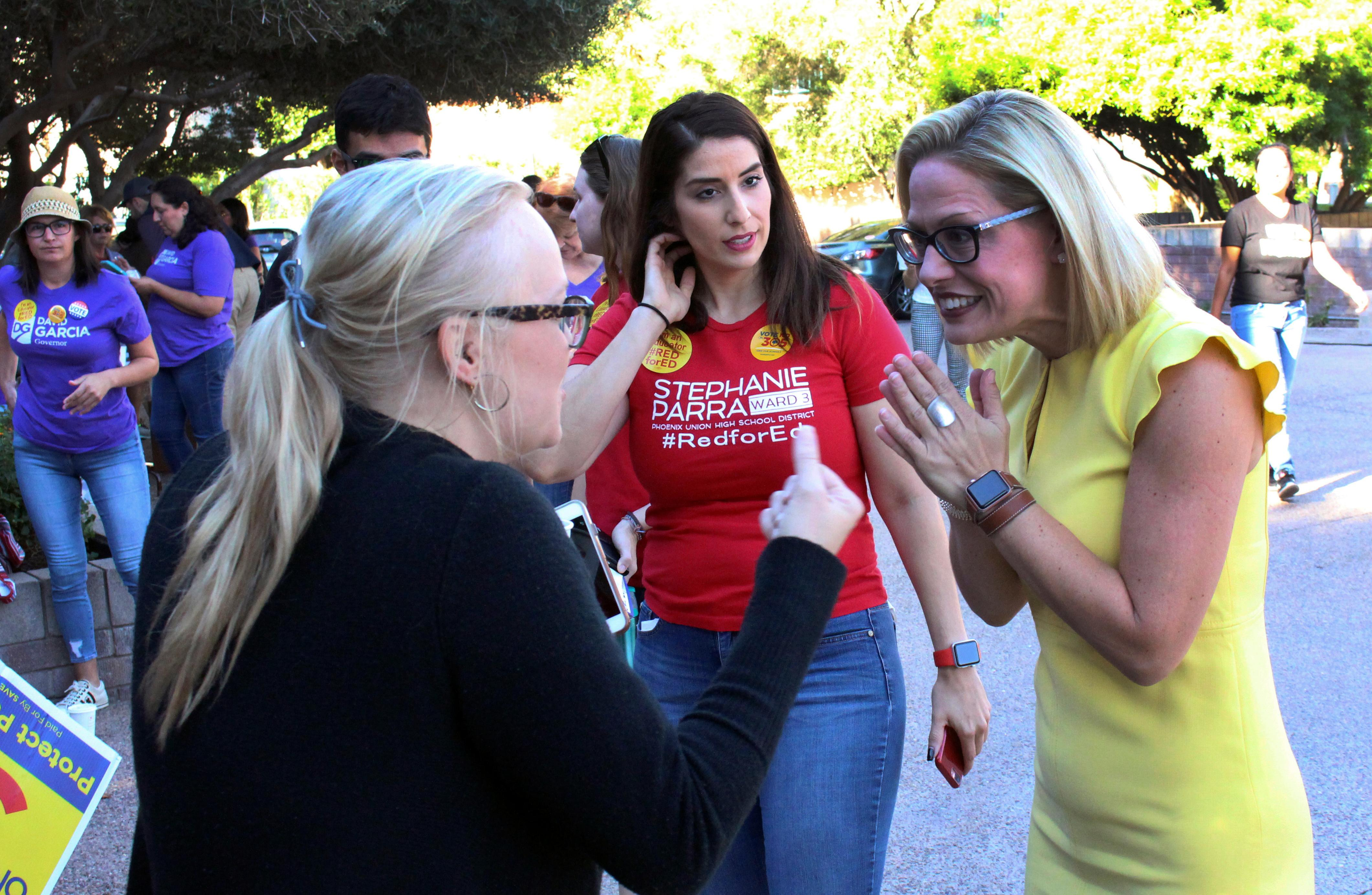 FILE--In this Nov. 3, 2018, file photo, a supporter, left, crosses her fingers as she talks with Democratic U.S. Senate candidate Kyrsten Sinema.{ } (AP Photo/Bob Christie, File)