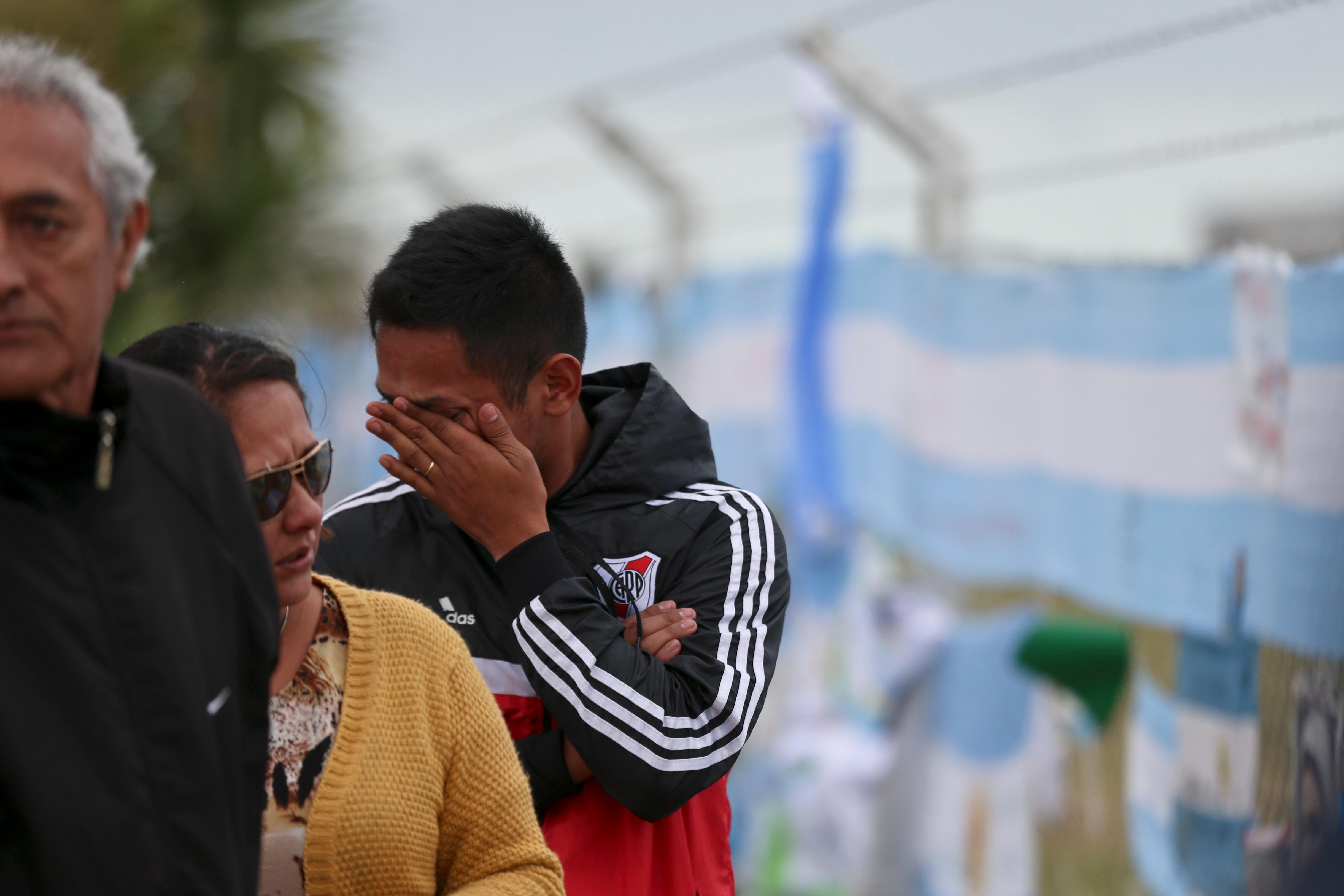A man outside the Mar de Plata Naval Base wipes a tear after the navy announced a sound detected during the search for the missing ARA San Juan submarine is consistent with that of an explosion, in Mar de Plata, Argentina, Thursday, Nov. 23, 2017. A Navy spokesperson said the search will continue until there is full certainty about the fate of the submarine, adding there was no sign the explosion might be linked to any attack. (AP Photo/Esteban Felix)