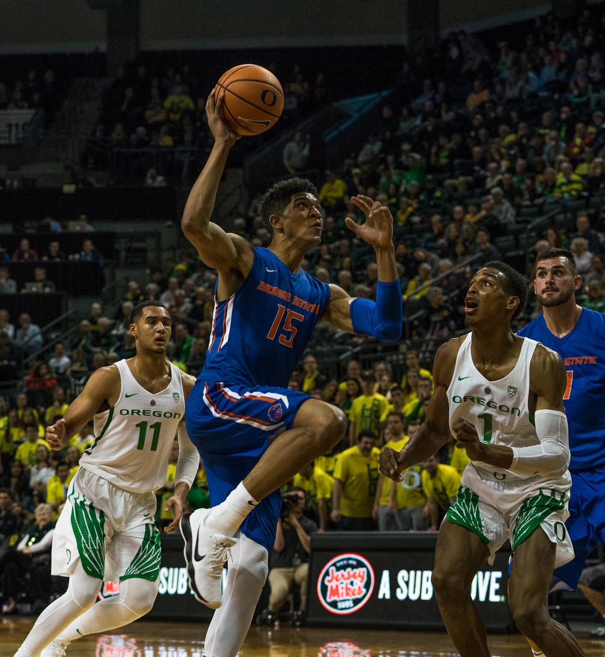 Boise State Bronco Chandler Hutchison (#15) drives to the basket before University of Oregon Ducks Kenny Wooten (#1) and Keith Smith (#11) can stop him. The Boise State Broncos defeated the University of Oregon Ducks 73 – 70 at Matthew Knight Arena in Eugene, Ore., on December 1, 2017. Photo by Kit MacAvoy, Oregon News Lab