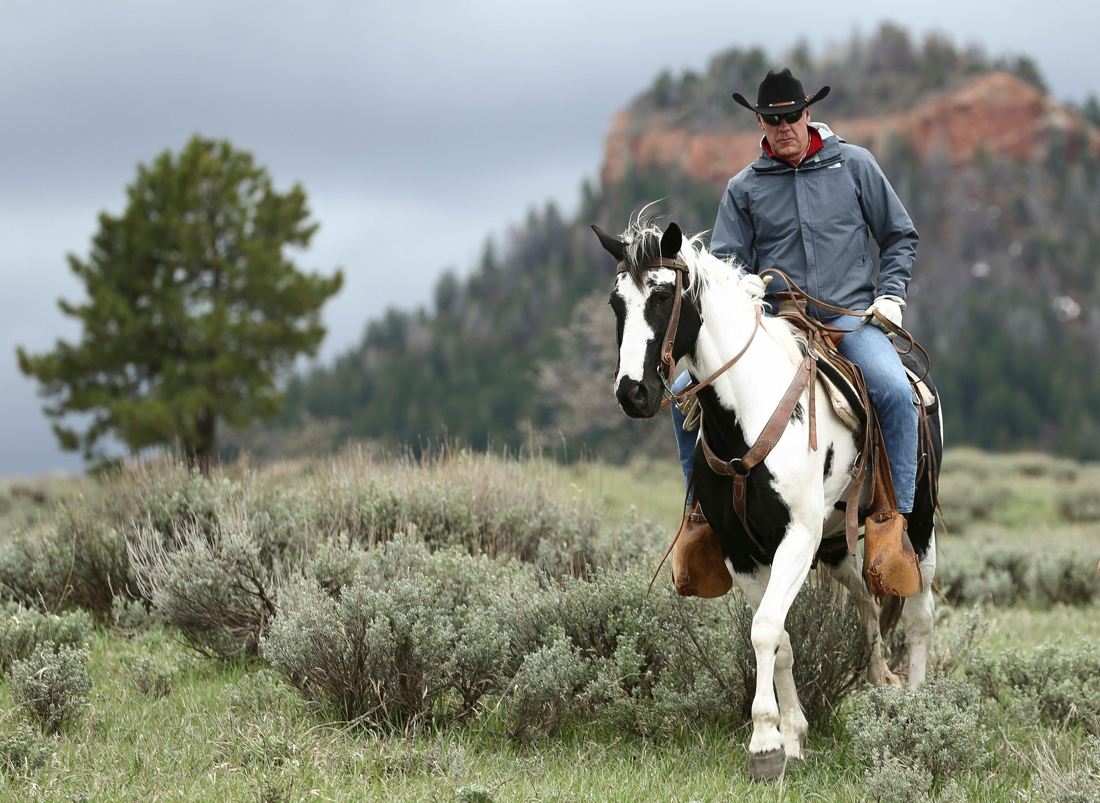 "FILE - In this May 9, 2017, file photo, Interior Secretary Ryan Zinke rides in the Bears Ears National Monument with local and state representatives in Blanding, Utah. Zinke is strongly disputing a claim by outdoor retailer Patagonia that President Donald Trump ""stole"" public land by shrinking two national monuments in Utah. (Scott G Winterton/The Deseret News via AP)"