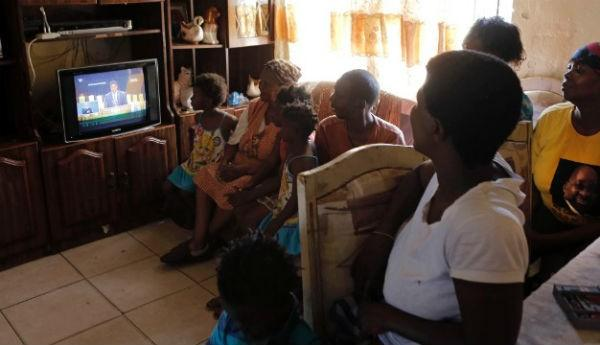 A family watches the funeral service from their home in Soweto, South Africa.Click the photo for the full story